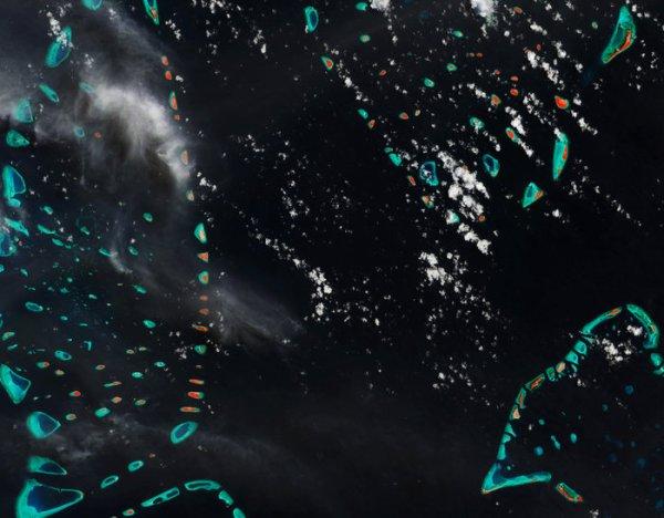 LA TERRE VUE DE L'ESPACE : LES JOYAUX DES MALDIVES ! Le satellite Sentinelle 2 Copernicus nous offre une partie des joyaux des Maldives, dans l'Océan Indien, à environ 700 kilomètres au sud-ouest du Sri Lanka. Cette nation se compose de plus de mille îles coralliennes réparties autour de plus d'une vingtaine d'atolls en forme d'anneau. Un certain nombre de ces petites îles est visible sur cette image ; les nuances de turquoise indiquent des bas-fonds où l'eau est transparente, parsemés de récifs coralliens, et la couleur rouge indique la végétation sur les terres émergées. Différentes formations nuageuses sont également visibles, et leurs apparences variées sont sans doute dues au fait qu'elles se trouvent à des altitudes différentes au-dessus de la surface. Comme beaucoup d'îles de faible altitude, les Maldives sont particulièrement vulnérables à l'élévation du niveau des mers et sont probablement le pays le plus plat sur Terre, sans zone située à plus de 3m d'altitude, et avec 80% des terres situées à moins de 1m d'altitude. Considérant que les données satellites montrent que les océans se sont élevés, en moyenne, de 4,8mm par an sur les cinq dernières années, la montée des eaux est une menace réelle pour ces joyaux insulaires ! (Sources ESA-Copernic Sentinel)