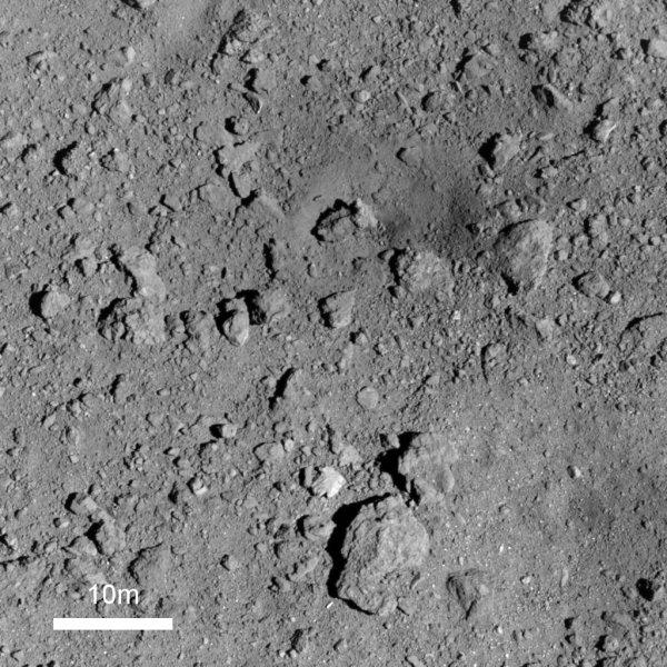 L'IMAGE & L'INFO ASTRO DU JOUR : A DES MILLIONS DE KILOMÈTRES DE LA TERRE, HAYABUSA 2 photographie le sol de RUYGU ! La mission japonaise Hayabusa 2 entre dans une nouvelle phase : aller arracher quelques roches supplémentaires à l'astéroïde Ryugu à l'endroit exact où elle a creusé un cratère. Elle a photographié de près, avec un bon degré de détail le petit cratère qu'elle a elle-même creusé le 5 avril en lui envoyant dessus un projectile métallique. Cette image permet aux équipes qui pilotent la sonde de déterminer à quel endroit il va être possible de larguer un marqueur afin de revenir, ultérieurement, collecter des échantillons. L'impact est la zone plus sombre située près du centre, dans le quart haut et droit de l'image. Un rocher d'environ 5m de large, qui affleurait sur une image à haute résolution prise avant le choc, a été entièrement mis au jour. Hayabusa 2 devra se stabiliser à 35 m de la surface avant de s'approcher jusqu'à 10 m et relâcher le petit module destiné à la guider ultérieurement. (Source JAXA)