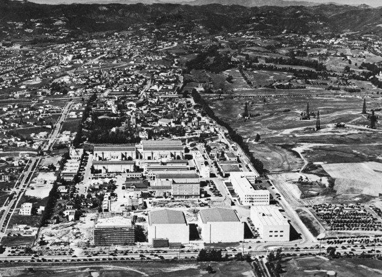 """STUDIO / 20th Century Fox Film Corporation ou 20th Century Fox (anciennement Twentieth Century-Fox Film Corporation de 1934 à 1985) est l'une des plus grandes sociétés de production cinématographique. Elle a été créée en 1915 en tant que Fox Film, par William FOX et fusionna ensuite avec Twentieth Century Pictures, créée en 1933 par Darryl F. ZANUCK (un ancien producteur de Warner Brothers) et Joseph SCHENCK (l'ancien président de United Artists). La Fox Film Corporation est créée en 1915 par le pionnier William FOX, par la fusion de ses deux sociétés fondées en 1913 : Greater New York Film Rental, une firme de distribution, et Fox (ou Box, suivant d'autres sources) Office Attractions Company, une compagnie de production. Ce regroupement entre distribution et production est un des premiers exemples d'intégration verticale. Un an auparavant, cette dernière avait distribué le dessin animé """"Gertie the Dinosaur"""" de Winsor McCAY. La Fox se concentra d'abord sur l'acquisition et la construction de théâtres. Ainsi, le cinéma était secondaire. Les premiers studios furent installés à Fort Lee, dans le New Jersey, mais en 1917, William FOX envoya Sol M. WURTZEL à Hollywood (Californie) pour créer un nouveau studio à la côte ouest, le climat étant, là-bas, plus accueillant et favorable à la création de nouveaux films. Avec l'introduction de technologies du son, la Fox acquis les droits du processus sound-on-film. Dans les années 1925-1926, la Fox acheta les droits sur les travaux de Freeman Harrison Owens, les droits américains du Tri-Ergon, système inventé par trois inventeurs allemands, et le travail de Theodore CASE. Avec ces trois brevets, la Fox créa Movietone, connu aussi sous le nom de « Fox Movietone ». Plus tard durant cette année, la société commença à produire des films avec des effets sonores, et l'année suivante créa l'hebdomadaire Fox Movietone News, publié jusqu'en 1963. La société ayant de plus en plus besoin d'espace, elle dut en 1926 acquérir 300 acres (1,2 k"""