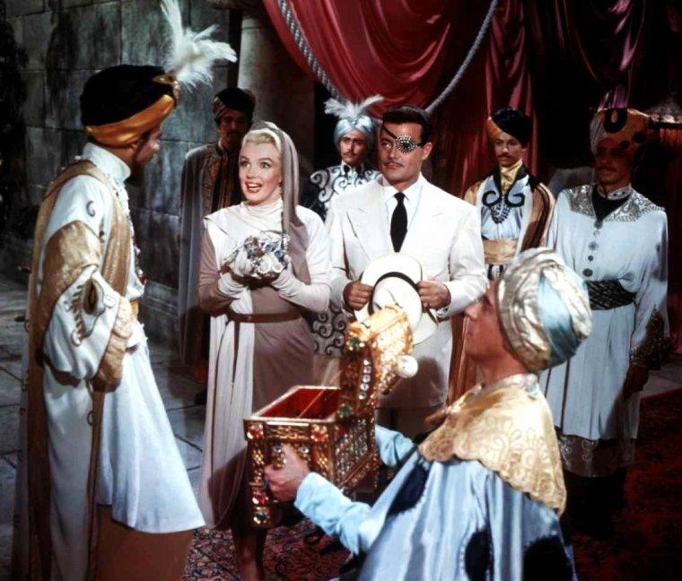 """FILM / """"Comment épouser un millionnaire"""" (How to Marry a Millionaire) est une comédie romantique américaine de Jean NEGULESCO sorti en 1953 et tourné en cinemascope. / SYNOPSIS / Schatze (Charlotte , en VF) PAGE (Lauren BACALL), une belle jeune femme, loue un très bel appartement à New York, qu'elle va partager avec deux amies, Pola DEBEVOISE (Marilyn MONROE) et Loco (Toctoc en VF) DEMPSEY (Betty GRABLE). Le propriétaire de l'appartement, monsieur DENMARK (David WAYNE), a des problèmes avec le fisc et a disparu de la circulation. Ce logement est un instrument dans leur stratégie à objectif unique, trouver un mari riche, voire très riche: Nothing under six figures a year (Rien en dessous du million par année) est le mot d'ordre. Elles n'ont pas sou qui vaille et vendent même le mobilier de l'appartement pour vivre! Le premier homme qu'elles rencontrent, Tom BROOKMAN (Cameron MITCHELL), est pompiste, ce qui n'entre pas tout à fait dans leurs plans (en fait, on apprend qu'il est un homme d'affaires richissime mais elles ne le sauront que bien plus tard). Il sera à plusieurs reprises remballé au téléphone par Schatze. Trois mois plus tard, grâce à Loco, elles sont enfin invitées à une soirée prometteuse en millionnaires divers: Schatze rencontre un texan riche et veuf, J.D. HANLEY (William POWELL) ; Pola un beau borgne à l'apparence d'aventurier fortuné, J. Stewart MERRILL (Alex D'ARCY) ; et Loco un homme d'affaires qui se présente lui-même comme étant """" l'homme le plus marié des USA """", Waldo BREWSTER (Fred CLARK). Tom BROOKMAN, qui a des vues sur Schatze, demande à ce que la maison de mode où travaillent les trois amies organise pour lui un défilé. Cela ne l'aide pas pour la conquérir. Loco part incognito en week-end dans le Maine avec son riche et marié Waldo ; elle y rencontrera Eben qu'elle croira un moment être un aisé propriétaire terrien. J.D. révèle son béguin à Schatze mais y renonce en raison de leur trop grande différence d'âge. Pola, alors qu'elle devait rej"""