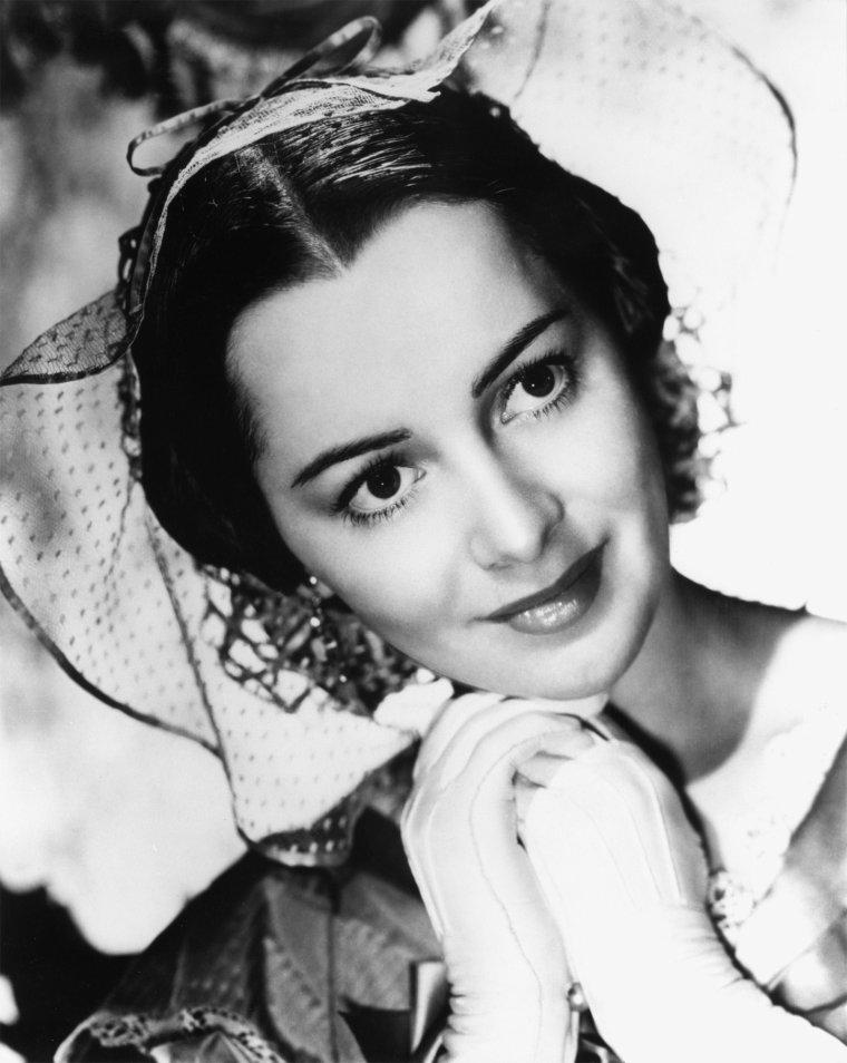 """Olivia Mary De HAVILLAND, née le 1er juillet 1916 à Tokyo (Japon), est une actrice américaine d'origine anglaise. Elle prête ses traits à Melanie WILKES dans """"Autant en Emporte le Vent"""" (Gone with the Wind) en 1939, et en reçoit une nomination pour l'oscar de la meilleure actrice dans un second rôle (que Hattie McDANIEL jouant Mama dans le même film, remportera)."""