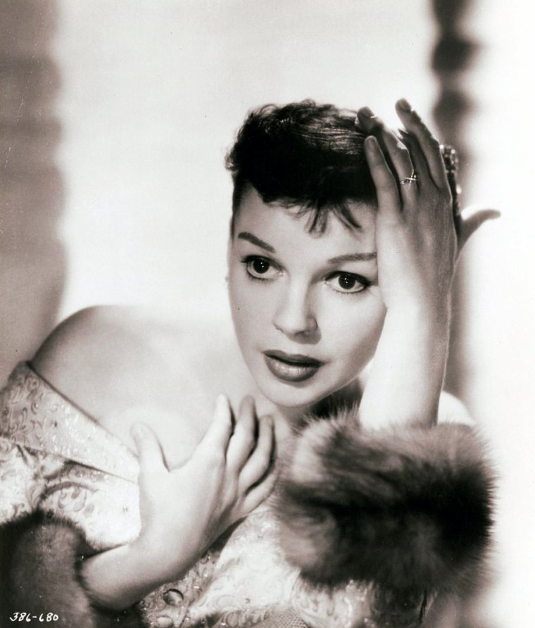 """Frances Ethel GUMM, dite Judy GARLAND, née le 10 juin 1922 à Grand Rapids (Minnesota) et décédée le 22 juin 1969 à Londres (Royaume-Uni), est une actrice et chanteuse américaine. En 1954, Sidney produit le film """"Une étoile est née"""" dans lequel elle joue le rôle d'une jeune artiste qui accède à la popularité grâce à l'aide d'une star sur le déclin, troisième des quatre versions tournées sur le même sujet. Le film eut un énorme succès auprès de la critique et du public malgré les mutilations opérées par la Warner Bros qui amputa le film de 90 minutes pour des raisons de distribution. Nommée aux Oscars la récompense échut à Grace KELLY."""