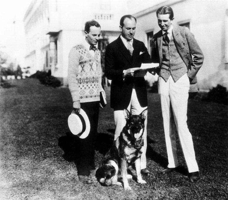 """Jack L. WARNER (2 août 1892 à London (Ontario) - 9 septembre 1978 à Los Angeles), était le président de la société de production Warner Bros. qu'il avait créé en 1923 avec ses trois frères, Harry, Sam et Albert. Ils ont commencé dans le cinéma avec un simple projecteur, par l'exploitation. Huit ans plus tard, ils se lançaient enfin dans la production. Leur premier film, """"My Four Years in Germany"""", réalisé par William NIGH, sort en 1918 ; c'est un triomphe. Ils ont innové le cinéma, en produisant par exemple le premier film contenant un son synchronisé : Le Chanteur de jazz avec Al JOLSON. On leur doit nombre de films. Ils ont également créé le groupe Warner Bros. Music. Peu avant 1953, le Warner theater, auparavant détenu par la Stanley Warner Theaters, est vendu à la Simon Fabian Enterprises, ce qui n'empêche le studio de perdre de l'argent. À la fin de 1953, le profit net du studio s'élève à 2 900 000 $ et se situe entre 2 et 4 000 000 $ pendant les deux années suivantes. En février 1956, Jack WARNER vend les droits de tous les films antérieurs à 1950 à l'Associated Artists Productions (qui fusionnera avec l'United Artists Television en 1958). En mai 1956, les frères WARNER annoncent qu'ils mettent en vente la Warner Bros. Jack, cependant, organise secrètement un syndicat — dirigé par le banquier Serge SEMENENKO — pour prendre 800 000 parts, soit 90 % de la compagnie. Après la vente conclue, Jack — grâce à son organisation — rejoint le syndicat de SEMENENKO et rachète toutes ses parts, soit 200 000 actions. Jack, désormais le plus grand actionnaire de la société — se nomme nouveau président de la Warner Bros. Harry et Albert découvrent le stratagème de leur frère mais il était déjà trop tard. Jack annonce que la compagnie et ses filiales seront « dirigées plus vigoureusement, dans le but d'acquérir la plupart des meilleures histoires, de nouveaux talents, et dans le but de produire un cinéma des plus fins possible »."""