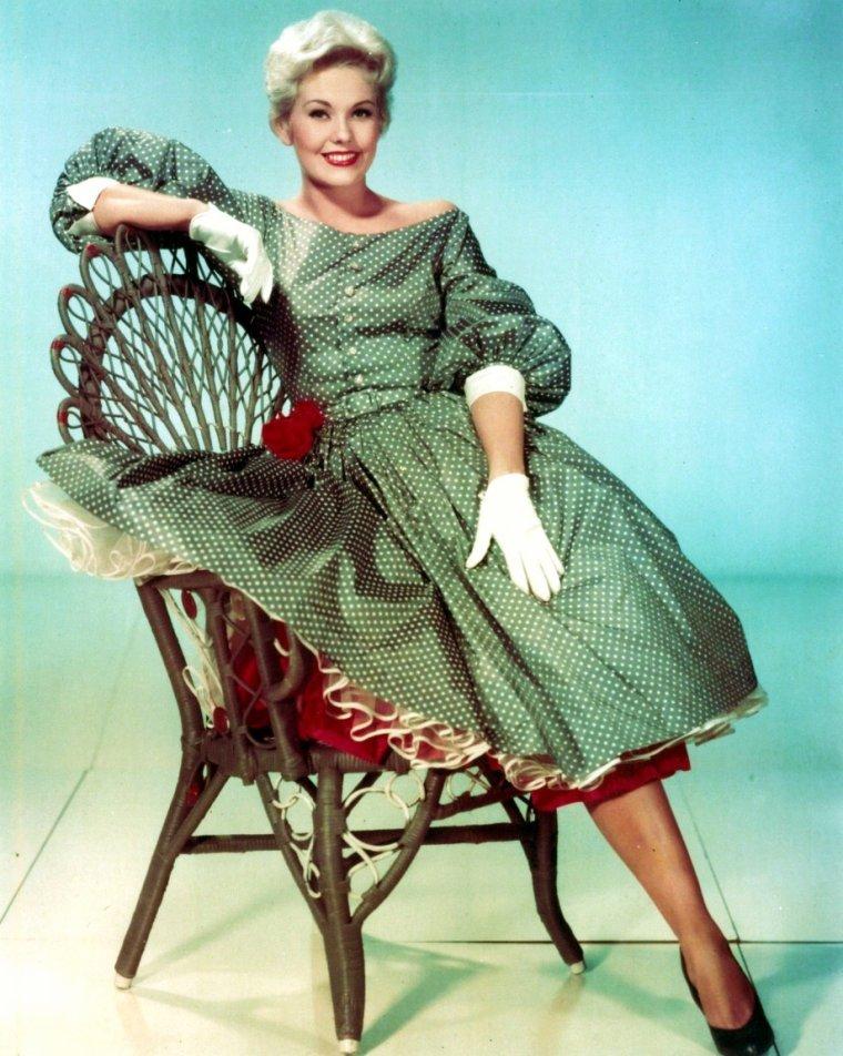 """Kim NOVAK (née Marilyn Pauline NOVAK, le 13 février 1933 à Chicago, États-Unis) est une actrice américaine. À l'âge de 21 ans, elle arrive à Hollywood et se fait engager par des dirigeants de la Columbia qui voyaient en elle une nouvelle Marilyn MONROE. Le succès s'ouvre à elle dès 1955 avec """"Picnic"""", pour lequel elle remporte le Golden Globe Award de la révélation féminine. Elle tourne deux films avec Frank SINATRA : """"L'Homme au bras d'or"""" en 1955 et """"La Blonde ou la Rousse"""" en 1957. L'année suivante, Alfred HITCHCOCK lui offre son plus grand rôle dans """"Sueurs froides"""" avec James STEWART qu'elle retrouvera la même année pour """"Adorable voisine"""". Elle joue aux côtés des plus grands: Kirk DOUGLAS (""""Liaisons secrètes"""", 1960), Jack LEMMON et Fred ASTAIRE (""""L'Inquiétante dame en noir"""", 1962), Dean MARTIN (""""Embrasse-moi, idiot"""", 1964) ainsi qu'Elizabeth TAYLOR (""""Le miroir se brisa"""", 1980). En 1991, à 58 ans, elle met fin à sa carrière d'actrice."""