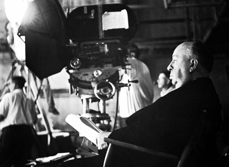 """BONUS PHOTOS du film """"Sueures froides"""" (1958) / Pour illustrer les scènes de vertige, Alfred HITCHCOCK utilise la caméra subjective, mais d'une façon particulière : alors qu'il filme, vers le bas, la profondeur de la cage d'escalier que James STEWART est censé voir avec angoisse, la caméra opère deux mouvements simultanés : un mouvement d'appareil vers l'arrière (travelling arrière) et un zoom avant (diminution de la longueur focale de l'objectif de la caméra). Le résultat de cet artifice technique appelé travelling compensé, utilisé ici pour la première fois dans un film, est une image qui se déforme, comme si la cage d'escalier s'allongeait."""