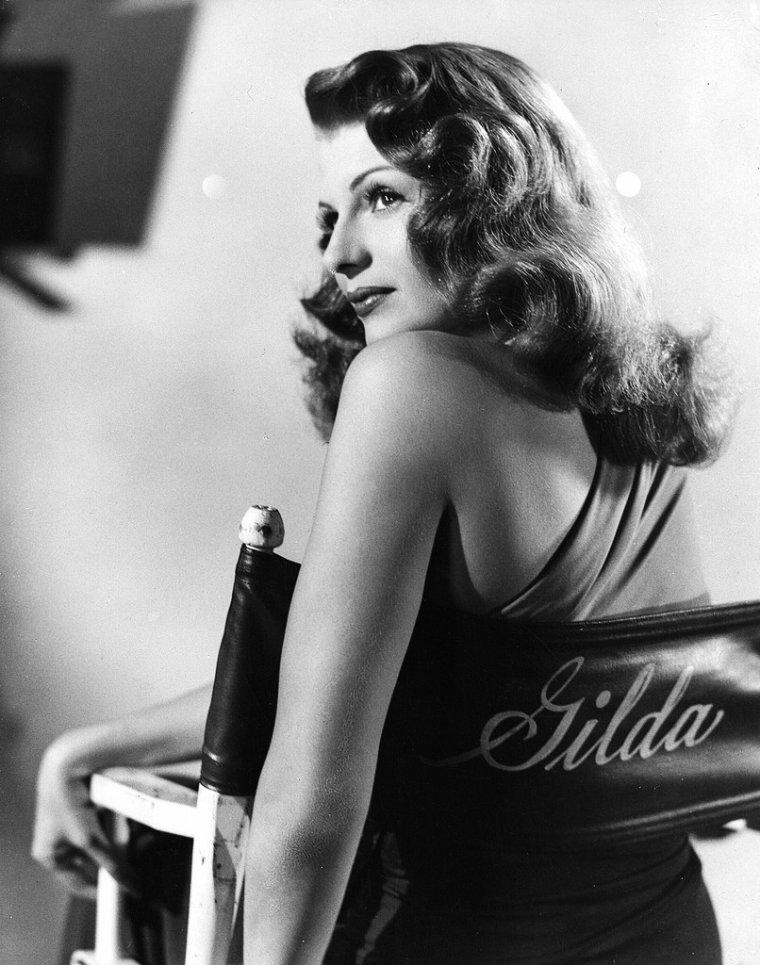 """FILM / """"Gilda"""" est un film américain de Charles VIDOR sorti en 1946. / SYNOPSIS / Johnny FARRELL, joueur professionnel, débarque à Buenos Aires, en Argentine. Il se lie d'amitié avec Ballin MUNDSON, le propriétaire d'un casino, dont il devient l'associé. À l'issue d'un voyage d'affaires, Ballin revient, accompagné de celle qu'il vient d'épouser : l'extraordinaire Gilda. Le hasard, la prédestination, veulent qu'elle soit précisément l'ex-fiancée de FARRELL. Ballin, suspectant l'ancienne liaison, confie à FARRELL la garde de Gilda. L'ancien amour renaît de ses cendres. FARRELL, en proie à la haine, la jalousie, subit l'inversion de sa passion amoureuse. Ballin, quant à lui, assoiffé de pouvoir, prépare l'organisation d'un trust international visant le monopole mondial du commerce d'un métal rare : le tungstène. Il réunit autour de lui un cartel d'hommes d'affaires, organisation secrète dont il est le chef. L'amour cependant, la passion qui le lie à Gilda, lui fait commettre les erreurs qui ruinent son plan. Gilda, devenue la veuve de Ballin, épouse FARRELL en secondes noces. Ce dernier prend la succession de Ballin à la tête du cartel du tungstène. Il accuse Gilda d'infidélité, et lui reproche de ne pas respecter la mémoire de son défunt mari. Gilda relève le défi de FARRELL. Elle provoque FARRELL et démontre à tous qu'elle est effectivement cette épouse infidèle qu'il a lui-même épousée. Coup de théâtre, Ballin, que l'on croyait mort, resurgit… Il compte bien reprendre Gilda, et menace d'éliminer FARRELL. Ballin est tué in extremis par Oncle PIO, l'employé-philosophe du casino et ange-gardien de Gilda."""