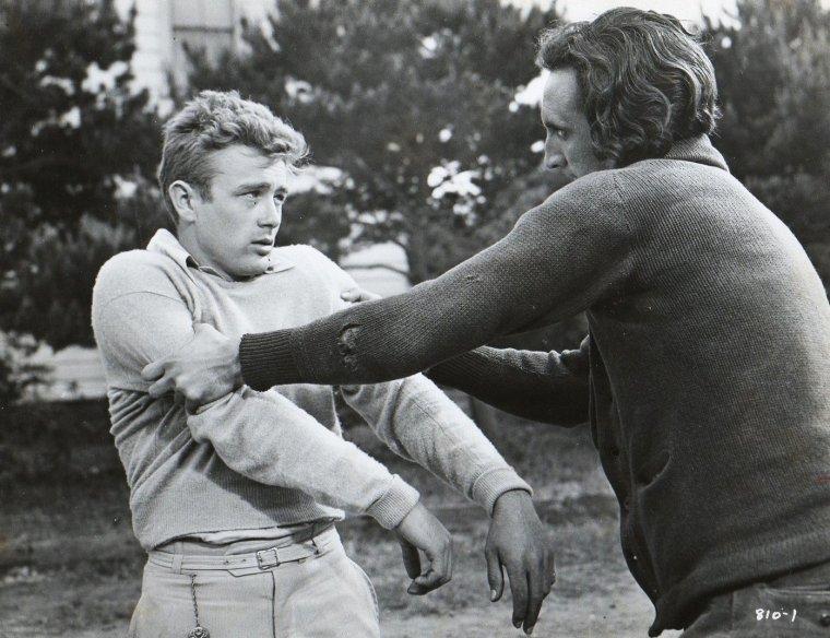 """FILM / """"À l'est d'Éden"""" (East of Eden) est un film américain d'Elia KAZAN, sorti en 1955, d'après le roman du même nom de John STEINBECK, publié en 1952, et dont le titre est inspiré du verset biblique relatant la fuite de Caïn, fils d'Adam, après le meurtre de son frère Abel. Genèse (4;16) : « Caïn se retira de devant l'Éternel, et séjourna dans le pays de Nôd, à l'est d'Éden. » C'est le premier film d'Elia KAZAN réalisé en couleurs et en Cinémascope. Il a reçu le Golden Globe du Meilleur film dramatique en 1956. Elia KAZAN et James DEAN ont été nommés aux Oscars en cette même année, respectivement pour les titres de Meilleur réalisateur et de Meilleur acteur. / SYNOPSIS / Année 1917. Aidé par ses deux fils, Cal et Aaron, Adam TRASK exploite ses terres à Salinas Valley. Les deux enfants croient que leur mère est morte, alors qu'elle a fui à la naissance des jumeaux. Cal, fils incompris, est convaincu que son père ne l'aime pas et qu'il n'est lui-même que l'incarnation du mal (qu'il voit en sa mère). Un jour, il apprend que sa génitrice vit dans la ville voisine, et qu'elle y tient un bar « louche », en fait une maison close. Parallèlement, Adam, le père, se ruine en faisant des affaires. Cal décide alors de faire fortune pour renflouer son père et gagner ainsi son amour. La fiancée d'Aaron, Abra, va alors doucement tomber sous le charme du jeune Cal, alors que la tournure des évènements est défavorable aux desseins du jeune homme. L'histoire du personnage recoupe celle de l'acteur, élevé dans une ferme, sans mère, et souffrant du manque d'amour de son père."""