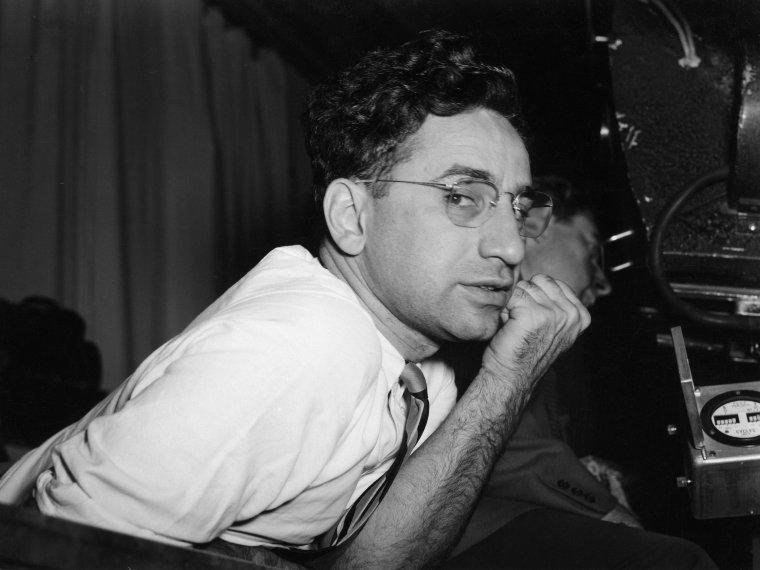 """Elia KAZANJOGLOUS (7 septembre 1909 - 28 septembre 2003), en turc Ilya Kazanoğlu, en grec Ilias Kazanoglou, dit Elia KAZAN, est un réalisateur, metteur en scène de théâtre et écrivain américain. Né à Istanbul en Turquie, fils d'un marchand de tapis grec. En 1911, la famille émigre aux États-Unis. Dans les années 1930, il s'intéresse au théâtre au sein du Group Theatre d'abord comme acteur, puis comme metteur en scène (notamment de """"Un tramway nommé Désir"""" de Tennessee WILLIAMS en 1947 et """"Mort d'un commis voyageur"""" d'Arthur MILLER, en 1949). Il est un des fondateurs, avec Cheryl CRAWFORD et Robert LEWIS, d'une école d'art dramatique, l'Actors Studio en 1947. Il se tourne vers le cinéma dans les années 40. Il réalise """"Un tramway nommé Désir"""" (1951), """"Viva Zapata"""" (1952), """"À l'est d'Éden"""" (1955), """"Sur les quais"""" (1954) qui est classé à la dix-neuvième place du Top 100 de """"l'American Film Institute"""" et """"l'Arrangement"""" (1969). Il épouse Barbara LODEN (réalisatrice de """"Wanda"""") en 1968. Il reçoit deux Oscars, comme meilleur réalisateur. Il reçoit également un Oscar pour l'ensemble de sa carrière en 1999. En 1934 il adhère au parti communiste et en est exclu en 1936. Plus tard, il participera à la chasse aux sorcières en dénonçant les gens du cinéma (dont certains de ses amis) appartenant à la gauche auprès de la commission des activités anti-américaines. KAZAN a d'ailleurs regretté cet épisode qui a entaché jusqu'à sa réputation de réalisateur. Il l'a mis en symbole dans le film """"Sur les Quais"""", et en particulier dans une scène aussi longue que transparente, au cours de laquelle Marlon BRANDO, une poutre sur le dos, suit son chemin de Croix devant les rangs des dockers trahis au début du film à cause de la mafia."""