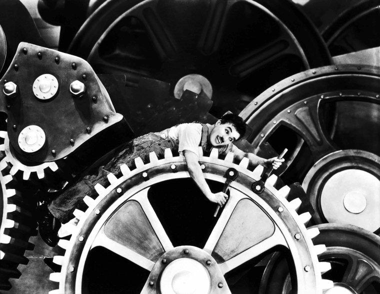 """FILM / """"Les Temps modernes"""" (Modern times) est une comédie dramatique américaine de Charlie CHAPLIN, sortie en 1936. Il s'agit du dernier film muet de son auteur et le dernier qui présente le personnage de Charlot, lequel lutte pour survivre dans le monde industrialisé. Le film est une satire du travail à la chaîne et un plaidoyer contre le chômage et des conditions de vie d'une grande partie de la population occidentale lors de la Grande dépression. Conditions imposées, selon CHAPLIN, par les gains d'efficacité exigés par l'industrialisation des temps modernes. Les vedettes du film sont Charlie CHAPLIN, Paulette GODDARD, qui fut pendant quelques années la compagne de l'auteur à la suite du tournage, Henry BERGMAN, Tiny SANDFORD et Chester CONKLIN. / SYNOPSIS / """"Les Temps modernes"""" montre la vie d'un ouvrier d'usine, employé sur une chaîne de production. Après avoir été soumis à divers mauvais traitements, gavé par une machine ou contraint à visser des écrous à un rythme effréné sur une chaîne de montage accélérée, Charlot est atteint d'une dépression nerveuse. Il est alors envoyé à l'hôpital. Après son rétablissement, devenu chômeur, Charlot est arrêté, par erreur, pour avoir fomenté une manifestation communiste, alors qu'il tentait en fait simplement de restituer un drapeau tombé d'un véhicule de livraison. En prison, il ingère accidentellement de la cocaïne, la prenant pour du sel. Dans l'état délirant qui s'ensuit, il est mêlé à une évasion à laquelle il met fin en mettant KO les autres condamnés. Il est alors acclamé en héros par les geôliers et libéré. Pourtant il se sent heureux en prison et voudrait y demeurer. Libéré contre sa volonté, il découvre combien la vie est rude, et rêve de retrouver sa confortable geôle après avoir provoqué une catastrophe sur un chantier naval. Il rencontre alors dans la rue une orpheline va-nu-pied (la « gamine »), interprétée par Paulette GODDARD, qui fuit la police après avoir volé un pain pour se nourrir. Pour sauver la jeune"""