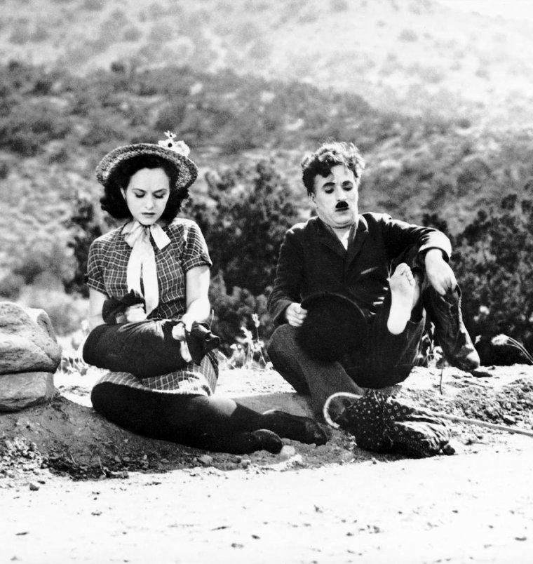 """Charles SPENCER CHAPLIN, Jr., dit Charlie CHAPLIN, est un acteur, réalisateur, producteur, scénariste, écrivain et compositeur britannique né à Londres le 16 avril 1889 et mort le 25 décembre 1977 à Corsier-sur-Vevey, en Suisse. Par son jeu de mime et de clownerie, il a su se faire remarquer, devenir l'un des plus populaires acteurs d'Hollywood et réaliser des courts puis des longs métrages qui l'ont rendu célèbre. Charlie CHAPLIN fut l'un des personnages les plus créatifs de l'ère du cinéma muet. Réalisateur, scénariste, producteur, monteur, et même compositeur de la musique de ses films. Sa carrière a duré plus de soixante-cinq ans, du music-hall en Angleterre, jusqu'à sa mort, en Suisse. Inspiré par l'acteur burlesque français Max LINDER, son personnage Charlot, pour les francophones, The Tramp (le vagabond) dans les pays anglo-saxons, apparaît pour la première fois dans Charlot est content de lui (""""Kid Auto Races at Venice""""), le 7 février 1914. C'est un sans domicile fixe qui a des manières raffinées dignes d'un gentleman, muni d'une canne de bambou, coiffé d'un chapeau melon, vêtu d'une veste étriquée et d'un pantalon qui tombe sur des chaussures trop grandes. Cette allure lui vaut la réputation de « vagabond » misérable et roué, asocial et obstiné, révolté et sentimental. Après la crise économique des années 30 et l'arrivée du parlant, CHAPLIN modifie son personnage, puis l'abandonne dans ses longs métrages des années 40 et 50, dans lesquels il continue (sauf pour son dernier film) à tenir les rôles principaux, ceux de personnages à la fois comiques, révoltés et sentimentaux, dénonçant l'injustice. Cet engagement social lui vaut des accusations de sympathies communistes lors de la période du maccarthysme. Il quitte les USA, qui ne lui remettent un oscar d'honneur qu'à la fin de sa vie. La vie publique et privée de Charlie CHAPLIN a fait l'objet d'adulation comme de controverses... Il conjugue tout cela dans """"Les Temps modernes"""" (1936), le dernier film muet de """