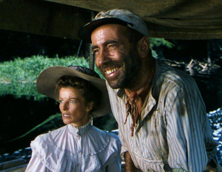 """FILM / """"L'Odyssée de l'African Queen"""" (The African Queen) est un film anglo-américain réalisé par John HUSTON et sorti en 1951, d'après le roman éponyme de C.S. FORESTER avec un duo d'interprètes principaux de premier plan : Humphrey BOGART et Katharine HEPBURN. Grâce à l'interprétation de son personnage de Charlie ALLNUTT dans ce film, H.BOGART remporte cette année-là l'Oscar du meilleur acteur. """"L'Odyssée de l'African Queen"""" a été sélectionné par """"Le National Film Registry"""" pour être conservé à la Bibliothèque du Congrès aux États-Unis pour son « importance culturelle, historique ou esthétique » en 1994. / SYNOPSIS / C'est l'histoire d'un homme et d'une femme de caractères opposés, lui fruste et bourru, elle délicate et un peu coincée, qui se rencontrent à l'occasion de la guerre, vivent une histoire très forte, apprennent à s'apprécier et finissent par s'aimer. Robert MORLEY et Katharine HEPBURN jouent les rôles de Samuel et Rose SAYER, frère et s½ur missionnaires méthodistes britanniques dans le village reculé de Kungdu en Afrique orientale allemande (aujourd'hui l'essentiel de la Tanzanie) au début de la Première Guerre mondiale en août-Septembre 1914. Samuel SAYER est le pasteur d'une congrégation anglicane. Il est secondé par sa soeur Rose, quadragénaire et un peu vieille fille. Leur seul contact avec l'Empire britannique est le passage régulier de Charlie ALLNUTT (joué par Humphrey BOGART), un baroudeur canadien. Il fait le coursier avec son bateau """"l'African Queen"""" sur la rivière pour le compte d'une exploitation minière belge. Samuel et Rose tolèrent assez mal son attitude frustre et parfois grossière. Charlie vient les avertir que la guerre a éclaté entre l'Allemagne et la Grande-Bretagne. Les SAYERS choisissent de rester, mais c'est pour assister à l'arrivée des allemands qui réquisitionnent les indigènes et brulent le village. Samuel proteste, mais il est frappé par un soldat allemand. Après le départ des soldats, Samuel est atteint de fièvre et meurt. """