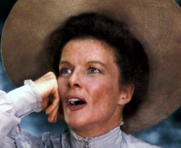 """Katharine HOUGHTON HEPBURN (née le 12 mai 1907 à Hartford dans le Connecticut, morte le 29 juin 2003 à Old Saybrook dans le Connecticut), est une comédienne américaine. Elle fut récompensée par l'Oscar de la meilleure actrice à quatre reprises, mais « Miss Kate », comme elle fut surnommée, ne prit même pas la peine de venir en chercher un. Dotée d'un fort tempérament, elle refuse les conventions ; HEPBURN compte parmi les grandes légendes hollywoodiennes. Éclectique et prolifique, elle excelle dans le registre de jeunes femmes loufoques ou de vieilles filles aigries (notamment dans les comédies de George CUKOR et Howard HAWKS) avant d'endosser le costume de souveraines d'Écosse et d'Angleterre (pour John FORD et Anthony HARVEY). Elle est classée par """"l'American Film Institute"""" comme la plus grande actrice de légende du cinéma américain en 1999. Elle n'a pas de lien de parenté avec Audrey HEPBURN, troisième de ce même classement. / Après un retour à Broadway triomphal et une tournée pour une pièce de SHAKESPEARE, Comme il vous plaira, John HUSTON lui propose de tourner un film avec Humphrey BOGART dans """"L'Odyssée de l'African Queen"""". Tourné en décors naturels à Biondo en République démocratique du Congo (alors Congo belge), le film fut éprouvant à cause des pénibles conditions climatiques, ce qui n'empêcha pas les deux acteurs de composer un duo haut en couleur qui fit la joie des spectateurs. Le film reçut quatre nominations aux Oscars pour John HUSTON, Katharine HEPBURN, James AGEE (scénario) et Humphrey BOGART qui obtint la précieuse statuette."""