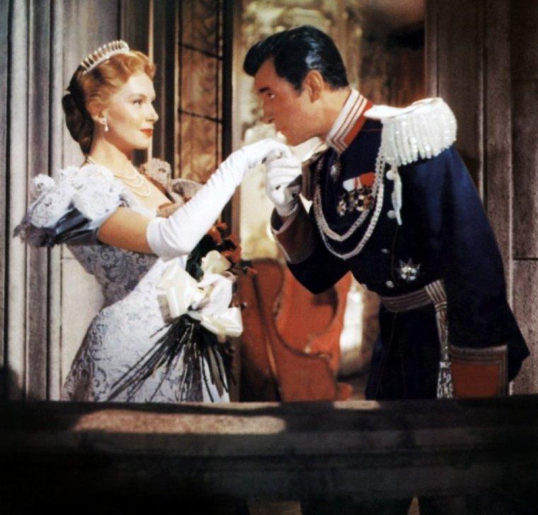 """FILM / """"Le Prisonnier de Zenda"""" (The Prisoner of Zenda) est un film américain réalisé par Richard THORPE, sorti en 1952. Cette version du roman d'Anthony HOPE est un remake quasiment plan pour plan de l'adaptation cinématographique de 1937. / SYNOPSIS / Rodolphe RASSENDYLL, un touriste anglais, arrive à Strelsau, capitale d'un pays imaginaire d'Europe Centrale, la Ruritanie. Il y rencontre un lointain cousin dont il est le parfait sosie, le prince héritier Rodolphe V. Celui-ci doit être couronné Roi le lendemain, mais à l'issue de la soirée que les deux parents éloignés passent ensemble, le futur souverain ne peut être ranimé : il a bu un vin drogué par une complice de son demi-frère, Michael De STRELSAU, lequel escompte se proclamer Régent du Royaume, en l'absence à la Cérémonie du Couronnement de Rodolphe V, puis faire assassiner ce dernier pour accéder ainsi au Trône. Mais deux fidèles du prince légitime, le Colonel ZAPT et Fritz Von TARLENHEIM, font accepter par RASSENDYLL qu'il joue le rôle de souverain au couronnement, grâce à cette providentielle ressemblance. Les choses se compliquent lorsque Rodolphe V, toujours endormi, est kidnappé le même jour par le mercenaire Rupert De HENTZAU ; en outre, RASSENDYLL tombe amoureux de la Princesse Flavia, promise en mariage au prince héritier..."""