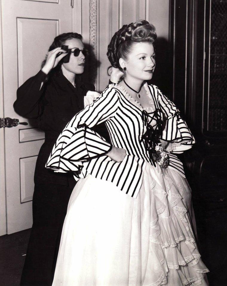 """Edith HEAD (28 octobre 1897 - 24 octobre 1981) est une costumière américaine de cinéma, qui a remporté huit Oscar de la meilleure création de costumes. Elle a travaillé pour les studios Paramount Pictures durant toute sa carrière. Attirée par Howard GREER, costumier en chef de Paramount Pictures, elle va vite s'imposer dans cette firme. Sa longue carrière à Hollywood lui a permis de remporter plus d'Oscars que n'importe quelle autre femme dans l'histoire du cinéma. Edith HEAD a fait des apparitions comme actrice en 1966 dans """"La Statue en or massif"""" de Russell ROUSE, et en 1973 dans un épisode du feuilleton """"Columbo"""", l'épisode """"Requiem pour une star"""" (Requiem for a Falling Star, 1973, saison 2, avec Anne BAXTER également), où elle joue son propre rôle, et où l'on voit les oscars qu'elle a remportés, sauf le dernier, remporté en 1974 pour """"L'Arnaque"""". Elle a écrit deux livres : """"The Dress Doctor"""" et """"How to Dress with Success"""". Elle est morte à 84 ans à Los Angeles d'une maladie de la moelle osseuse. Un des rares techniciens du cinéma à jouir d'une certaine notoriété auprès du public, Edith HEAD associe son nom au glamour de toute une époque du cinéma américain. Elle participe à la plupart des productions de prestige de la Paramount jusqu'en 1967, date à laquelle elle signe un contrat avec Universal. Il arrive que ses créations pour le cinéma provoquent des effets de mode dans la vie réelle. Le manteau de plumes de paon de Hedy LAMARR dans """"Samson et Dalila"""" (1949) de Cecil B. DeMILLE, le fameux vison de Bette DAVIS pour """"Eve"""" (1950) de Joseph Leo MANKIEWICZ, les pantalons cigarette d'Audrey HEPBURN dans """"Sabrina"""" (1954) de Billy WILDER sont tous signés Edith HEAD. Durant sa longue collaboration avec Alfred HITCHCOCK, elle habille notamment Grace KELLY et Kim NOVAK. Elle excelle dans l'univers masculin et les costumes d'époque, comme en témoignent """"L'Arnaque"""" (1973) de George ROY-HILL ou """"L'Homme qui tua Liberty Valance"""" (1962) de John FORD. Dans son dernier film, """""""