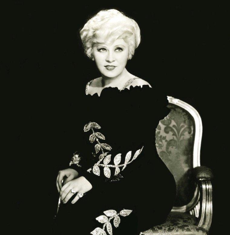 """Mary Jane WEST dite Mäe WEST (17 août 1893 - 22 novembre 1980) était une actrice américaine sex-symbol des années 1920 à 1940. Se produisant aussi dans des revues musicales, elle contribua au succès de la danse shimmy. Mary Jane WEST naît à Woodhaven, une petite ville de la classe moyenne située dans le Queens, quartier de New York. Elle déménage successivement dans différents endroits du Williamsburg & Greenpoint à Brooklyn, où elle suit une scolarité à l'Erasmus Hall High School. Elle est la fille de John Patrick WEST (1865–1935) et Matilda """"Tillie"""" DELKER-DOELGER (1870–1944). Elle a une s½ur et un frère, nommés Mildred Katherine « Beverly » WEST (1898–1982) et John Edwin WEST (1900–1964). Son père était un boxeur du nom de Battlin' Jack WEST qui a ensuite préféré exercer la fonction de policier. Il a d'ailleurs fini par devenir détective et a fondé sa propre agence. Sa mère était mannequin et fabricante de corsets. La famille était protestante, en dépit des origines juives de la mère, bavaroise. C'est une femme libre qui s'est affirmée dans ses choix et sa carrière, fortement désapprouvés par sa grand-mère paternelle, Irlandaise d'origine romaine et très catholique. Mäe WEST commence sa carrière à l'âge de 5 ans. / ANECDOTES / En référence à sa généreuse poitrine, les aviateurs américains de la Seconde Guerre mondiale avaient surnommé Mäe WEST leurs gilets de sauvetage. Ceux-ci fonctionnaient en se gonflant d'air comprimé et en donnant à leur torse un volume supplémentaire… De nos jours les gilets de sauvetage gonflables sont encore appelés couramment des Mäe WEST, même en dehors des pays anglophones. / Au musée DALI de Figueres (Catalogne), une salle porte son nom. Vu du bon endroit, le mobilier de cette salle représente son visage. Elle fait donc figure de mythe de l'entre-deux-guerres selon Salvador DALI. / Mäe WEST possédait un physique bien à elle qu'elle mettait en valeur avec des idées… bien à elle. Outre le port de corsets serrés afin d'affiner sa taille """