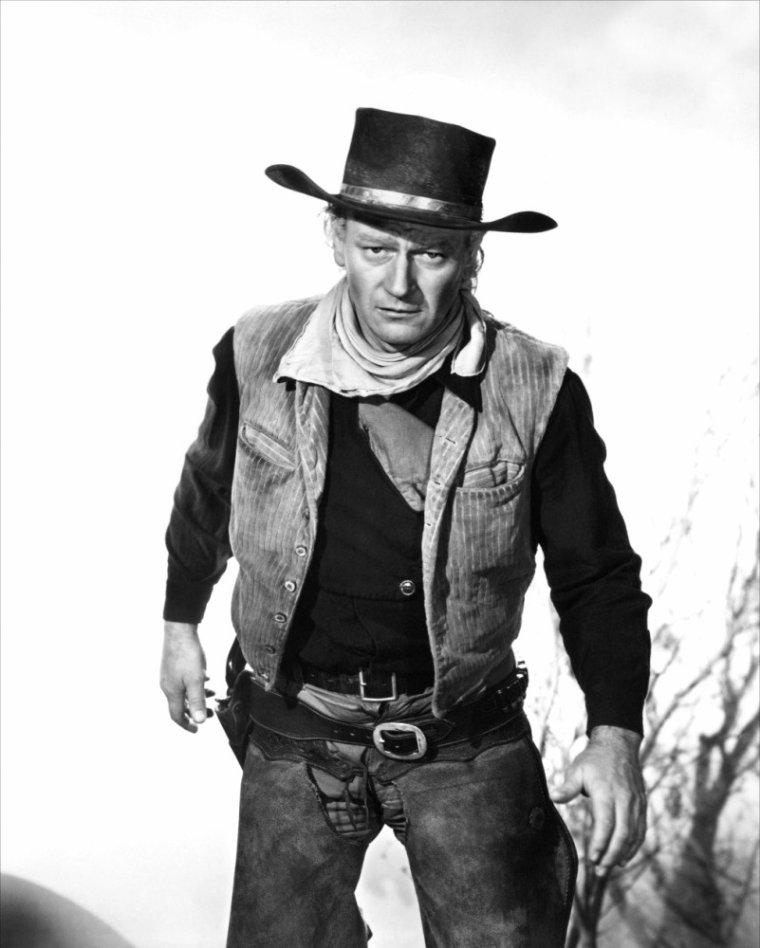 """Marion MITCHELL MORRISON, dit John WAYNE, né le 26 mai 1907 à Winterset dans l'Iowa, aux États-Unis, et mort le 11 juin 1979 à Los Angeles, est un acteur, réalisateur et producteur américain. S'il a joué dans des films policiers, des films de guerre et quelques comédies romantiques, c'est dans ses nombreux westerns que John WAYNE s'est réellement imposé, sous la direction de deux réalisateurs particulièrement : John FORD (""""La Chevauchée fantastique"""", """"Le Massacre de Fort Apache"""", """"La Charge héroïque"""", """"Rio Grande"""", """"L'Homme tranquille"""", """"La Prisonnière du désert"""" ou encore """"L'Homme qui tua Liberty Valance"""") et Howard HAWKS (""""La Rivière rouge"""", """"Rio Bravo"""", """"El Dorado"""" ou """"Rio Lobo""""). Il tourna également plusieurs films avec Henry HATHAWAY dont """"Cent dollars pour un shérif"""", qui lui valut en 1970 l'unique Oscar de sa carrière. En 1960, il passa derrière la caméra pour réaliser une fresque historique d'envergure, """"Alamo"""", relatant les derniers jours de Davy CROCKETT et ses compagnons lors de la guerre d'indépendance du Texas. Huit ans plus tard, il coréalisa """"Les Bérets verts"""", film engagé justifiant l'intervention américaine au Viêt Nam. Ses deux réalisations reflètent l'engagement personnel de John WAYNE, républicain et ardent patriote. Classé 13ème plus grande star de légende par """"l'American Film Institute"""" en 1999, John WAYNE est certainement un des acteurs les plus représentatifs du western, une incarnation à lui seul de l'Amérique conquérante. Surnommé « The Duke », il reste toujours aujourd'hui grâce à ses films le symbole d'une certaine virilité. Il interpréta ce rôle d'homme viril, dur, solitaire et un peu machiste tout au long de sa carrière, ce qui lui fit déclarer """"J'ai joué John WAYNE dans tous mes films et ça m'a plutôt pas mal réussi"""" ."""