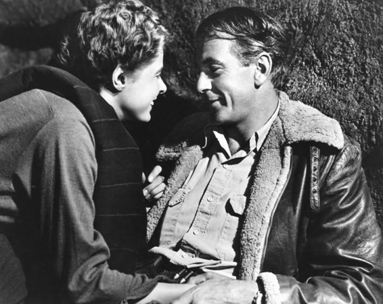"""FILM / """"Pour qui sonne le glas"""" (For Whom the Bell Tolls) est un film américain réalisé par Sam WOOD en 1943, avec Gary COOPER, Ingrid BERGMAN, Akim TAMIROFF, Arturo De CORDOVA ou encore Katina PAXINOU qui remporta l'Oscar de la meilleure actrice dans un second rôle. / SYNOPSIS / Ce film est tiré du roman d'Ernest HEMINGWAY """"Pour qui sonne le glas"""". Venu combattre aux côtés des républicains lors de la Guerre d'Espagne, l'américain Robert JORDAN est chargé de faire sauter en Castille un pont défendu par les fascistes afin de couper la route à l'armée franquiste. Il tombe amoureux de Maria, une des résistantes du groupe dirigé par Pablo et sa femme Pilar. / COMMENTAIRES / De la séquence d'ouverture à la séquence de fermeture, le film est traversé par trois thèmes majeurs. Le thème de la mort. Robert a pour mission de faire sauter le pont et il sait qu'il n'y survivrait pas. Pablo, en connaissant la mission, sait immédiatement qu'elle conduira à leur mort. Sordo, aussi, y voit cette issue inévitable. Presque tous les personnages contemplent leur propre mort. Le thème de la camaraderie accompagne la perspective de la mort, sacrifice des personnages pour une juste cause. Robert JORDAN, Anselmo et les autres sont prêts à le faire, comme «tout homme de bien le ferait», avec des accolades fréquentes qui renforcent l'impression d'un compagnonnage intense. Après avoir annoncé à Joaquim l'exécution de toute sa famille, tout le monde l'embrasse et déclare être maintenant sa famille. Cet amour des uns pour les autres se porte aussi à la terre d'Espagne, dès le début jusqu'à la fin. C'est un hymne à la vie traversée par la mort, la vie simple et poignante décrite comme «sentir son c½ur battre contre le sol tapissé d'aiguilles de pin». Le thème du suicide chez tous les personnages où chacun préfère se donner la mort ou être achevé par un camarade plutôt qu'être capturé. L'image finale est Robert JORDAN, blessé et incapable de suivre ses compagnons, qui se prépare à mourir en proté"""