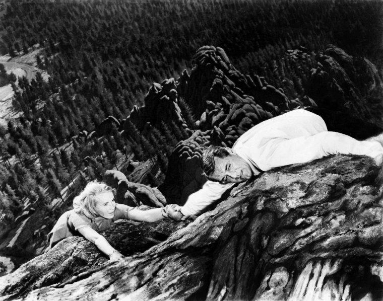 """Archibald Alexander LEACH, plus connu sous son pseudonyme de Cary GRANT, né le 18 janvier 1904 à Bristol (Angleterre) et mort le 29 novembre 1986 à Davenport (Iowa), est un acteur américain d'origine britannique. Il a été naturalisé citoyen des États-Unis le 26 juin 1942. Après une adolescence troublée, ce bricoleur habile, de grande taille (il mesurait 1,87m) avait la particularité d'avoir un menton dit « en fesse d'ange », devient chanteur dans les comédies musicales de Broadway à New York. Son accent britannique mi-aristocratique mi-ouvrier de représentant de commerce fit de lui un spécialiste du genre dit « foldingue », genre comédie de boulevard marathon (screwball comedy). Charmant mais peu stable, il a été marié cinq fois. Il tournera dans plusieurs films d'Alfred HITCHCOCK qui, bien connu pour ne pas aimer les acteurs, dira de lui « qu'il était le seul acteur qu'il ait jamais aimé de toute sa vie ». Ian FLEMING s'est inspiré de sa séduction, et de son look soigné pour créer le personnage de James BOND. En 1961, il fut le premier acteur à avoir été approché par Ian FLEMING pour le rôle de James BOND, mais il refusa le rôle parce qu'il avait 58 ans à l'époque, et se sentait trop vieux pour incarner le célèbre agent secret. À la fin de sa vie, il fera des tournées aux États-Unis appelées """"A Conversation with Cary GRANT"""" au cours desquelles étaient projetés des extraits de ses films suivis de débats. """"L'American Film Institute"""" l'a classé deuxième acteur de légende. / """"La Mort aux trousses"""" contient quelques scènes d'anthologie, dont la moindre n'est pas celle où THORNHILL (GRANT) pense avoir rendez-vous avec l'agent fantôme KAPLAN en rase campagne. Au lieu de la rencontre qu'il prévoyait, il se retrouve être la proie d'un petit avion dont les occupants finissent par le mitrailler. La séquence entière constitue un condensé de l'art et du génie du réalisateur. / Cary GRANT ne voulait plus tourner et disait avoir pris sa retraite lorsque HITCHCOCK le supplia de ve"""