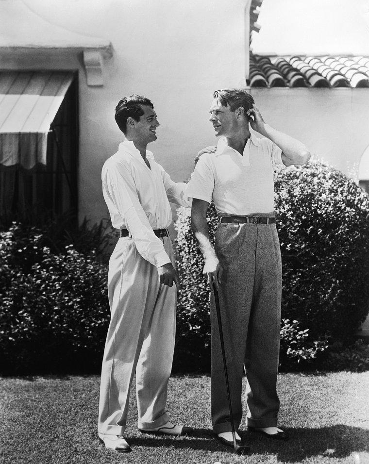 """LA BELLE HISTOIRE / Quel est le comble de l'amour fou ? Se suivre dans la mort. Randolph SCOTT (1898-1987), archétype du héros de western, n'aura survécu que trois mois à Cary GRANT (1904-1986), l'acteur au menton en fesses d'ange. Cette romantique coïncidence, mentionnée dans toutes leurs biographies, suggère ce qui n'a jamais vraiment été reconnu: Cary et Randolph furent, en tout cas au début, «profondément et follement amoureux», selon Richard BLACKWELL, couturier d'Hollywood avant d'en devenir l'échotier indiscret. Leur «belle amitié» qui dura toute la vie n'est pas sans rappeler les tourments des deux cow-boys de """"Brokeback Mountain"""". Pourtant, c'est plutôt du côté de """"Certains l'aiment chaud"""", comédie foldingue où tout est possible à condition d'avoir de l'humour, que fait penser leur relation pleine de fantaisie, d'ambiguïté et de tolérance. Il faut dire que les deux hommes avaient une certaine inclination à en rajouter pour énerver les commères. Randolph, un soir de dîner mondain, dédicace son menu: «A mon époux Cary… Randy !» De son côté, l'acteur fétiche de HITCHCOCK nourrit la rumeur en affirmant qu'il préfère les sous-vêtements féminins, plus confortables. Si Cary GRANT et Randolph SCOTT ne se sont jamais «outés», ils ne se sont pas cachés non plus, du moins avant la mise en place du code HAYNES à Hollywood au milieu des années 30 qui interdisait toute allusion à l'homosexualité. Le couple, qui s'est formé en 1931, a même vécu sous le même toit pendant douze ans, s'amusant des rumeurs et se laissant photographier en situation conjugale: dans leur intérieur glamour, en tête-à tête languissant devant la mer, en Apollon à l'entraînement de boxe ou en maillot de bain sur le plongeoir de leur piscine. La Paramount, qui les lança dans """"Hot Saturday"""", voyait dans cette ambiguïté une manière habile de faire la promotion de leurs poulain. Leur cohabitation ne fut pourtant pas sans problème… pour leurs femmes. L'actrice Viriginia CHERRILL, première épouse de Cary """
