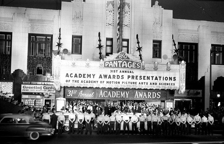 OSCAR DU CINEMA / Les Oscars du cinéma (Academy Awards) sont des récompenses cinématographiques américaines décernées chaque année depuis 1929 à Los Angeles et destinées à saluer l'excellence des productions mondiales du cinéma. L'attribution de ces distinctions dans les domaines choisis pour représenter les métiers de la création cinématographique (réalisation, interprétation, scénario, technique) est organisée, gérée et contrôlée par l'association professionnelle Academy of Motion Picture Arts and Sciences (AMPAS), créée par Louis B. MAYER, alors patron de Metro-Goldwyn-Mayer, dans le but de promouvoir les productions des studios, établir une feuille de route dans le financement et la distribution de longs métrages sur le sol américain et aider à la médiation dans les conflits sociaux. En 2012, elle compte plus de 6 000 membres et représentants possédant le droit de vote. Parmi l'ensemble des membres, qui regroupe notamment des producteurs, des scénaristes, des réalisateurs, des techniciens et d'autres personnes exerçant une profession liée à l'industrie du cinéma, les acteurs représentent près d'un quart des votants. Les collèges de votants sont au nombre de 15 (avec une seizième branche d'élargissement). Le recrutement se fait par cooptation : les nouveaux membres sont invités à le devenir et doivent, pour cela, recevoir le parrainage d'au moins deux adhérents de leur branche de métier et l'aval du conseil des gouverneurs de l'Académie. Les invitations sont lancées après évaluation d'une contribution majeure au monde du cinéma. Les personnes ayant été nommées ou récompensées par un Oscar sont généralement admises de manière automatique. Même si l'association est ouverte aux personnalités mondiales, l'essentiel de ses membres reste originaire des États-Unis. Les récompenses décernées sont destinées aux films et aux personnes qui représentent, aux yeux de l'Académie, les meilleurs réalisations, ouvrages et travaux artistiques de l'année écoulée. Si cette compétiti