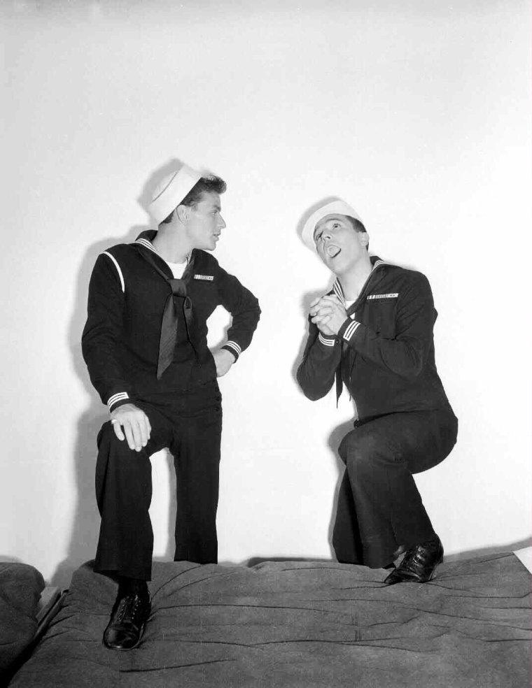 """Eugene CURRAN KELLY (nom de scène Gene KELLY) est un acteur, chanteur, réalisateur et danseur américain né le 23 août 1912 à Pittsburgh, en Pennsylvanie, et mort à Los Angeles le 2 février 1996. Il est probablement, avec Fred ASTAIRE, la personnalité masculine la plus marquante de la comédie musicale hollywoodienne des années 1950. Il inscrit son nom à plusieurs classiques du genre, tels que """"Le Pirate"""", """"Un Américain à Paris"""" et """"Brigadoon"""" de Vincente MINNELLI, """"Un jour à New York"""" et """"Chantons sous la pluie"""" qu'il co-réalise avec Stanley DONEN, """"Les Girls"""" de George CUKOR ou encore """"Les Demoiselles de Rochefort"""" de Jacques DEMY. Il réalise ensuite plusieurs films, dont la comédie musicale """"Hello Dolly"""" avec Barbra STREISAND. Puis, avec le déclin de la comédie musicale, ses prestations se raréfient. Il retrouve son éclat et sa popularité passés dans deux documentaires, """"That's entertainment Part I et II"""", à la fin des années 1970. En 1999, il est classé quinzième plus grande légende du cinéma par """"L'American Film Institute"""". En outre, """"Chantons sous la pluie"""" et """"Un Américain à Paris"""" reviennent régulièrement en tête des classements des plus grandes comédies musicales au cinéma. En 1944, le studio « prêta » l'acteur à la Columbia pour laquelle il tourna """"La Reine de Broadway"""" avec Rita HAYWORTH et assura la chorégraphie des numéros de danse. Le film eut un succès retentissant et marqua le début des années de gloire de la danse au cinéma. Gene KELLY avait su donner un style particulier à ses chorégraphies. Dans son film suivant, """"Escale à Hollywood"""" avec Frank SINATRA, Gene KELLY fit encore preuve d'innovation dans la chorégraphie qu'il mit en place, notamment dans la scène où on le voit danser avec Jerry la souris en dessin animé. La scène fut rejetée au départ par le studio, mais finalement acceptée et reste à ce jour un modèle du genre. Gene KELLY fut nommé pour l'Oscar du meilleur acteur pour ce film qui fut un grand succès."""