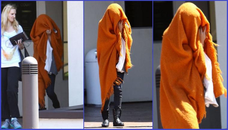 11/08/13: Selly se cachent sous une couverture orange pour quitter un des bureaux a Tarzana, en Californie.