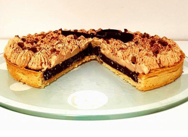 Tarte sucrée aux noisettes, chocolat caramel et ganache carambars saupoudrer de cacao , copeaux de chocolat et éclats de caramel