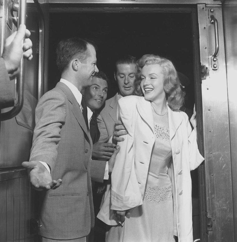 """1949 / En juin 1949, Marilyn MONROE est en voyage à travers les Etats-Unis pour promouvoir le film """"Love Happy"""". Elle se rend à New York, chargée par le magazine Photoplay de participer à la remise du concours """"Dream Home"""" (""""Maison de Rêve"""") organisé par le magazine. Marilyn est accompagnée des acteurs Don DEFORE et Lon McALLISTER qui la suivirent dans le train et lors de la remise du prix qui se déroule à Warrensburg, New York. Marilyn, ayant entendue dire qu'à New York il faisait toujours beaucoup plus froid qu'à Los Angeles, était vêtue d'une robe en laine noire, alors qu'il faisait une chaleur accablante et ce, dès le trajet en train. Sur place, Lester COWAN lui acheta une robe blanche en coton, achetée chez un grossiste à New York, qu'elle porta tout le reste du séjour. Elle remet les clés à la gagnante, Virginia McALLISTER, accompagnée de son petit garçon. Puis elle visite la maison qui contient tout l'équipement moderne de l'époque. Les photos de l'événement paraîtront dans l'édition de Novembre 1949 du magazine Photoplay."""