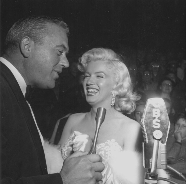"""1953 / Première de """"How to marry a millionaire"""" au Fox-Wilshire Theater, où elle put prendre toute la mesure de la qualité de son interprétation. Son ami le maquilleur Whitey SNYDER et la coiffeuse Gladys RASMUSSEN l'aidèrent à se  préparer pour cette soirée. Son amie l'actrice Shelley WINTERS était également présente à cette  soirée.  Au cocktail précédent la première (qui eut lieu chez le scénariste Nunnally JOHNSON avec sa femme Doris, Humphrey BOGART et Lauren BACALL), Marilyn, tendue, avait bu plusieurs bourbon-soda et était visiblement éméchée quand elle traversa la foule hurlante pour entrer dans le théâtre. Pour Marilyn, cette soirée fut un triomphe : « C'est la plus belle soirée de ma vie. C'est comme lorsque j'étais petite et que je rêvais qu'il m'arrivait des choses merveilleuses. A présent, elles sont arrivées. Mais c'est drôle comme le succès peut attirer sur vous la haine des gens. Je souhaite que cela ne se produise pas. Ce serait formidable de profiter du succès sans lire la jalousie dans les yeux de ceux qui vous entourent. ». Elle devait penser à Natasha LYTESS aussi bien qu'à toutes les autres actrices qui étaient autant de rivales. Coach attitrée et habilleuse occasionnelle, Natasha devait se révéler, selon Marilyn, « complètement cinglée de réclamer à mon avocat 5 000 $ pour couvrir ses frais chirurgicaux. J'en ai vraiment assez et je me rends bien compte que c'est une femme très rusée. Mais, je ne veux pas qu'elle perde son travail à la Fox ». Ce soudain changement d'attitude de Marilyn envers Natasha s'expliquait. Après plus de vingt films tournés sous sa tutelle, il était clair qu'aucun collègue de Marilyn n'avait jamais approuvé la tactique de ce coach ou même apprécié ses interventions. Ensuite, les plaintes s'étaient tellement accumulées que Marilyn ne pouvait plus les ignorer. De plus, elle était en train de prendre de l'assurance ; enfin, elle souhaitait faire plaisir à Joe. Elle assista ensuite à la soirée donnée chez le réalisateur Jea"""