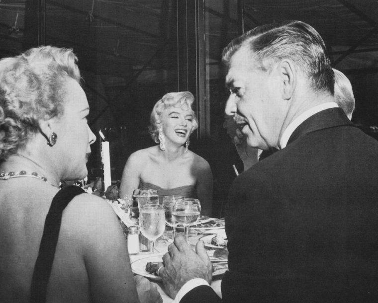 """1954 / by Sam SHAW... Pour fêter la fin du tournage de « The seven year itch », Charles FELDMAN organisa une réception au restaurant """"Romanoff's"""" à Beverly Hills en l'honneur de Marilyn. Elle était accompagnée du photographe Sam SHAW. Entre autres des quatre-vingt invités de marque, il y avait Billy WILDER , Humphrey BOGART, Lauren BACALL, Claudette COLBERT, William HOLDEN, James STEWART, Doris DAY, Susan  HAYWARD, Gary COOPER, Loretta YOUNG, George BURNS, Clifton WEBB, Clark GABLE, Darryl ZANUCK, Jack WARNER, Sam  GOLDWYN, Tom EWELL et Sidney SKOLSKY ; tous la complimentèrent : Marilyn était enfin acceptée du tout Hollywood. Mais ce n'était pas seulement un geste amical et généreux de la part de Charles FELDMAN : La première des raisons était que cette soirée était la réponse aux récriminations, qui ne faisaient qu'empirer avec le temps, de ZANUCK contre Marilyn, ses absences, ses retards et ses bafouillages qui obligeaient l'équipe technique à effecteur de nombreuses prises d'une même scène. Pour FELDMAN, ces reproches étaient ridicules. Le jour même où elle achevait « There's no business like show business » elle partait pour New York tourner « The seven year itch». Son divorce l'avait rendue indisponible une semaine, certes, mais elle avait travaillé quinze jours consécutifs. Il ajouta que comme ZANUCK le savait bien, vingt prises ou plus étaient chose courante pour un réalisateur méticuleux."""