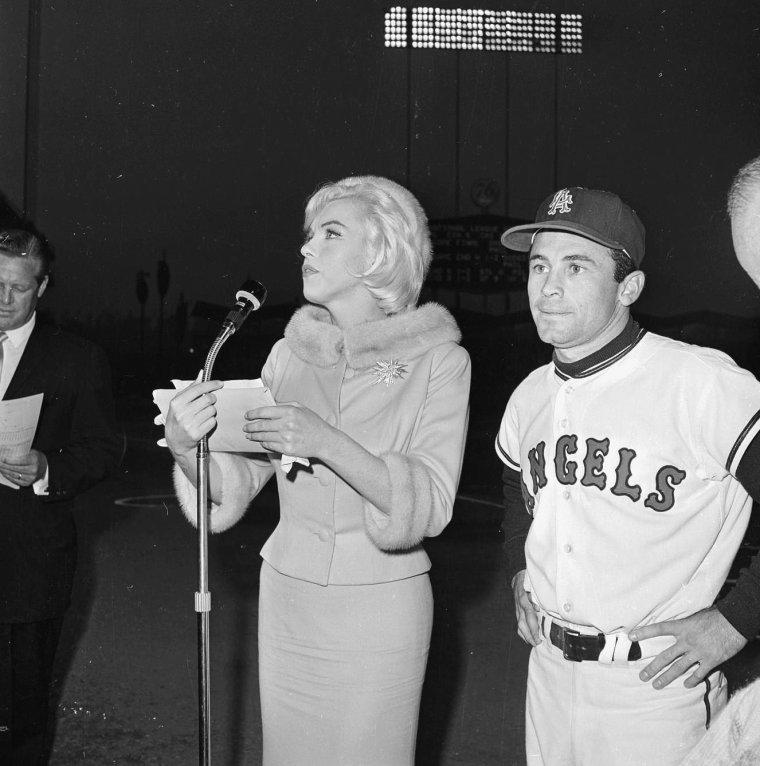 """1962 / Marilyn quitte la Fox après la petite fête organisée pour son 36ème anniversaire sur le plateau du film """"Something's got to give, en compagnie de l'acteur Wally COX. Ce soir là, elle assiste, avec le costume qu'elle porte dans la journée (un tailleur de soie beige avec toque en fourrure assortie), à une soirée au """"Chavez Ravin Dodger Stadium"""" de Los-Angeles, pour un match de base-ball donné au profit de la  dystrophie musculaire ; elle lançe la première balle. Mais elle prend froid, et de retour chez elle, vers 22 heures, se plaint de céphalées ; elle souffre à nouveau d'une sinusite..."""