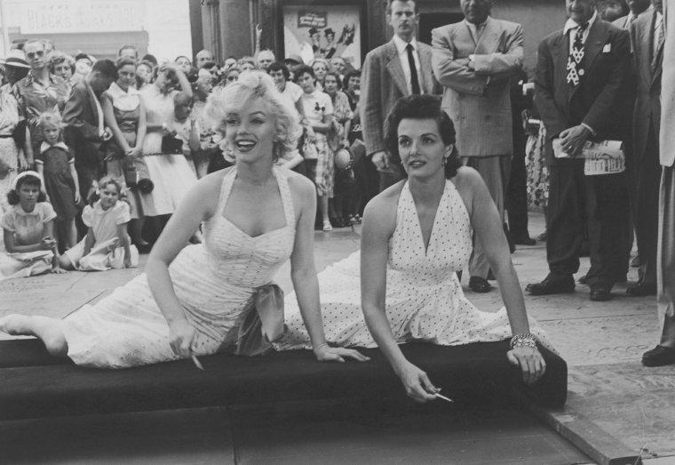 """1953 / Le 26 juin 1953, Jane RUSSELL et Marilyn laissent leurs empreintes de pieds et de mains dans le ciment devant le """"Grauman's Chinese Theatre"""" à Los Angeles. Cela faisait plusieurs mois maintenant que le film """"Gentlemen prefer blondes"""" était fini. Cependant, il n'était pas encore sorti ! Mais il était indéniable que Marilyn était devenue une Star. Nous pouvons considéré cette consécration comme une avant première des plus ingénieuse pour le lancement de """"Gentlemen prefer blondes"""". Pour Marilyn un rêve de gosse prenait vie. Elle n'a jamais vraiment parlé de cet instant pourtant il est sûr qu'il représente un moment très important dans sa vie. Elle a dû ressentir une joie immense. Plusieurs anecdotes courent. La première est que Marilyn voulait un vrai diamant sur le """"i"""" de Marilyn. Mais pour des raisons évidentes, un faux fut mis en place... qui fut volé très rapidement. La deuxième concerne les empreintes en elles-même. Marilyn aurait suggéré qu'elle pose ses fesses sur le ciment et Jane sa poitrine... Vrai ou faux, c'est en tout cas vraiment très amusant."""