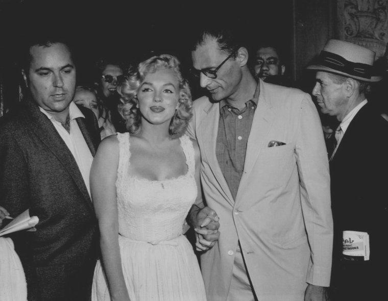 """1957 / Marilyn jardinait dans son jardin à Amagansett, quand elle ressentit une violente douleur au ventre. Arthur appela une ambulance, mais étant à près de deux cents kilomètres de New York, ils n'arrivèrent qu'à midi au """"Doctor's Hospital"""" de New York. Les Dr Bernard BERGLASS et Hilliard DUBROW l'opérèrent : comme ils l'avaient craint, Marilyn faisait une grossesse extra-utérine. Ils ne purent sauver le bébé : pour protéger la vie de Marilyn, il fallait interrompre la grossesse. Marilyn perdit donc son enfant. Terriblement déprimée, elle resta dix jours à l'hôpital. Elle voyait dans la perte de son enfant, le signe qu'il y avait quelque chose qui n'allait pas chez elle. MILLER pensa que peut-être, un bon rôle pourrait la faire s'estimer d'avantage. Le samedi 10 août : Marilyn et Arthur quittèrent l'hôpital et se rendirent à Amagansett où elle se reposa. C'était une triste épreuve pour elle. La perte de son enfant affecta gravement sa confiance en soi et son sentiment de maturité. Ce fut leur ami et photographe Sam SHAW (qui était allé la voir à l'hôpital), qui conseilla à MILLER de faire de sa nouvelle, « The misfits», un long métrage, spécialement pour Marilyn. Il convainquit MILLER que ce serait le moyen idéal de prouver que Marilyn était une actrice dramatique de talent.  Ayant lu la nouvelle de MILLER, il pensait que ce sujet ferait un excellent film pour Marilyn. Jusqu'alors, MILLER avait toujours refusé d'écrire des scénaris. Mais il commença à écrire le scénario de « The misfits », d'après sa nouvelle du même nom. Il dût développer le personnage de Roselyn, rôle de Marilyn, qu'il jugeait trop falot. En créant ce personnage, Arthur croyait sincèrement qu'il avait fait une chose merveilleuse pour Marilyn, mais elle ne réagit pas en ce sens. Elle ne voulut même pas s'engager pour ce rôle. Dans les derniers jours de l'été, les MILLER retournèrent à Manhattan."""
