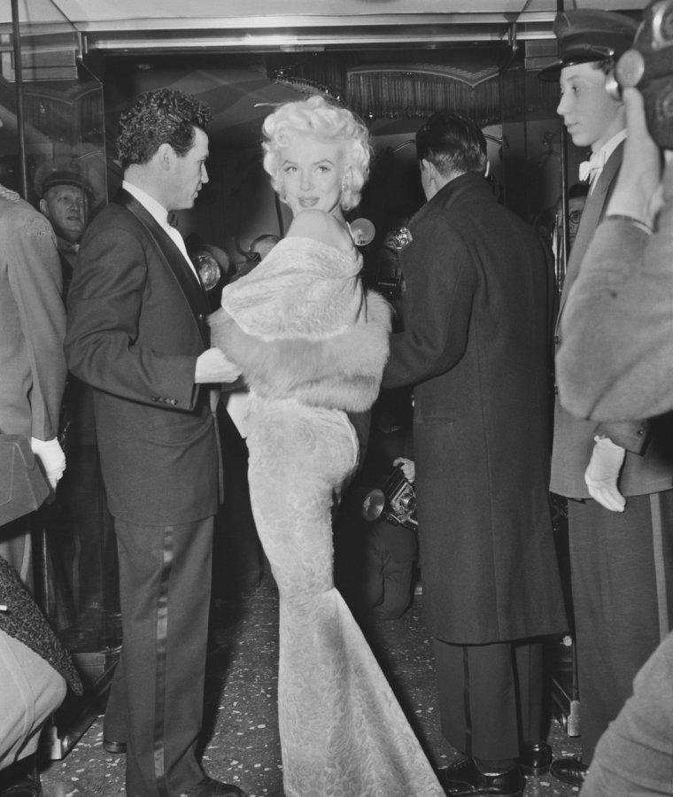 """1955 / Le 9 mars 1955, au """"Astor Theater"""" de New York, Marilyn participe comme ouvreuse à une séance de bienfaisance, la première du film """"East of Eden"""" (A l'est d'Eden) qu' Elia KAZAN avait tourné pour la Warner Bros. Marilyn s'était portée volontaire pour servir d'ouvreuse, surnommée """"Usherette"""", portant une écharpe telle une Miss. Les bénéfices de cette représentation reviennent à l'Actors Studio ; Marilyn pose avec beaucoup de dévotion devant l'attroupement des photographes. Elle est aussi submergée par l'émotion, devant l'amour que lui porte le public: les gens se sont attroupés en criant son nom et réclament des autographes. Accompagnée de Milton GREENE et escortée de son agent new-yorkais Jay KANTER ; Marilyn discute avec Sammy DAVIS Jr., le journaliste Earl WILSON, la femme de Milton, Amy GREENE, le photographe Sam SHAW, le comédien et animateur de show Milton BERLE et l'acteur Richard DAVALOS (qui joue le rôle du frère de James DEAN dans """"A l'est d'Eden""""). L'actrice Julie HARRIS, qui joue aussi dans le film, était présente. Le grand absent de la soirée reste James DEAN, qui aurait préféré rester loin de l'agitation médiatique pour passer la soirée dans un bar de Manhattan. Certains prétendent que Marilyn aurait vraiment souhaité le rencontrer personnellement et qu'une rencontre aurait eu lieu plus tard. James DEAN va mourir tragiquement six mois à peine après cette soirée, le 30 septembre 1955."""