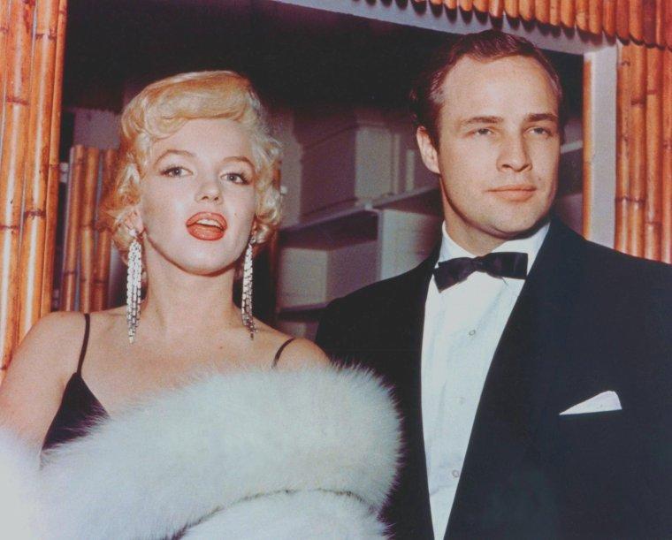 """1955 / Le 12 décembre 1955, Marilyn se rend à la première du film de Daniel MANN """"The Rose Tattoo"""" (La Rose Tatouée) à """"l'Astor Theatre"""" de New York, avec dans les rôles principaux, Anna MAGNANI et Burt LANCASTER, pourtant absents à cette première new-yorkaise. Marilyn, resplendissante dans une robe noire assortie de longs gants noirs et d'un fourreau blanc, portant de longues boucles d'oreilles, pose avec malice et glamour devant les photographes et les caméramens venus spécialement filmer l'arrivée des stars. Après la projection du film, les célébrités se rendent à une soirée tenue au """"Sheraton Astor Hotel"""", dans le but de récolter des fonds pour """"l'Actors Studio"""" (100 000 dollars seront obtenus), lors d'un dîner et d'une soirée dansante où les reporters sont nombreux. Marilyn est escortée par Marlon BRANDO, avec qui elle vit alors une aventure amoureusement secrète à cette période. Parmi les invités, se trouvent Lee, Paula et Susan STRASBERG, le couple ROSTEN, Arthur JACOBS, Jayne MANSFIELD et Arthur MILLER, qui sera photographiée publiquement pour la première fois au côté de Marilyn."""