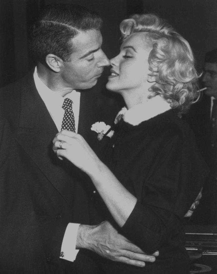 """1954 / 14 Janvier 1954, Marilyn et Joe DiMAGGIO se marient civilement à l'Hôtel de ville de San-Francisco (Polk street). Elle porte à l'occasion un tailleur marron chocolat avec un col d'hermine blanche. Joe voulait épouser Marilyn religieusement, mais l'archevêque de San Francisco, John MITTY, refusa de reconnaître la validité de son divorce avec Dorothy ARNOLDS, sa première épouse. Il n'y eut donc qu'un mariage civil. Ils y pensaient bien sûr depuis un certain temps, mais ne prirent la décision que deux jours avant. Ils souhaitaient un mariage aussi discret que possible, et Marilyn ne prévint le studio qu'une heure avant la cérémonie. Malgré cela plus de cent journalistes et reporters envahirent l'entrée et les couloirs de l'hôtel de ville. Elle n'avait pas d'invités personnels; seule la famille et les amis de Joe assistaient à la cérémonie, célébrée par l'officier municipal, le juge Charles S.PERRY. La cérémonie débuta à 13h48 et se termina trois minutes plus tard. Le témoin de Joe était Reno BARSOCCHINI ; les autres invités étaient Jean et Lefty O'DOUL, Tom DiMAGGIO et sa femme Lee. A la sortie de la mairie, ils furent assaillis pas les journalistes puis ils sautèrent dans la Cadillac bleu nuit de Joe en route pour leur lune de miel : une nuit au """"Clifton Motel"""", à Paso Robles, puis deux semaines dans une maison cachée dans la montagne (la maison de l'avocat de Marilyn, Lloyd WRIGHT), en dehors d'Idyllwild, près de Palm Springs. La vie fut aussi difficile qu'avant le mariage, bien que tous deux étaient prêts à des concessions mutuelles. Joe était très méticuleux, aussi bien chez lui que dans ses affaires; Marilyn était exactement le contraire. Il préférait la vie calme à San Francisco, elle avait besoin de Los Angeles; il était taciturne et réservé, elle était impulsive et sujette aux éclats ; il aimait passer son temps avec sa famille et ses amis ou passer une soirée à regarder la télévision, elle, qui avait abandonné les soirées hollywoodiennes, souhaitait des"""