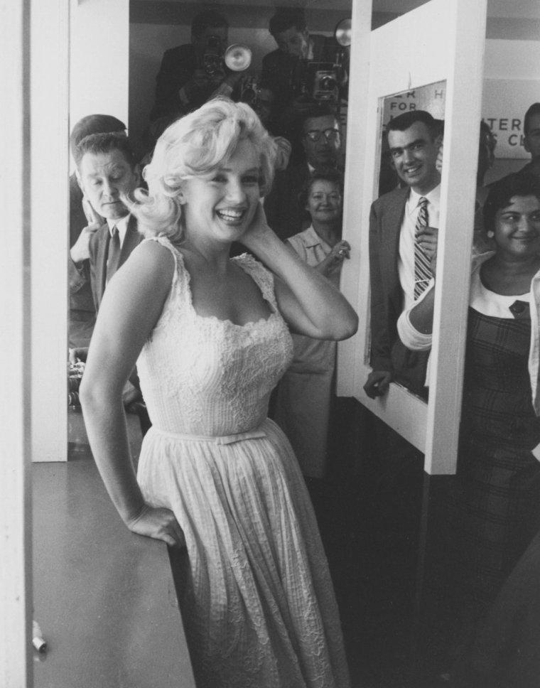 """1957 / La souriante Marilyn débarque en hélicoptère le 2 juillet 1957 à New York, en provenance de sa résidence d'été à Amagansett, mais avec deux heures et demie de retard, pour participer à la cérémonie marquant le début de construction d'un nouvel immeuble, le """"Sidewalk Superintendents Club"""" au """"Rockefeller Center"""". D'ailleurs Lawrence D. ROCKFELLER, membre et directeur du """"Rockefeller Center"""", qui devait acceuillir Marilyn à son arrivée, est finalement parti pour un rendez vous de déjeuner, après avoir attendu plus de deux heures, juste cinq minutes avant l'arrivée de Marilyn. ROCKFELLER déclara : """"Je n'ai jamais attendu aussi longtemps dans ma vie pour qui que ce soit"""". Marilyn s'est ensuite rendue en plein centre de New York pour allumer la mèche d'un bâton de dynamite, marquant l' inauguration de l'historique site """"Time & Life building""""."""