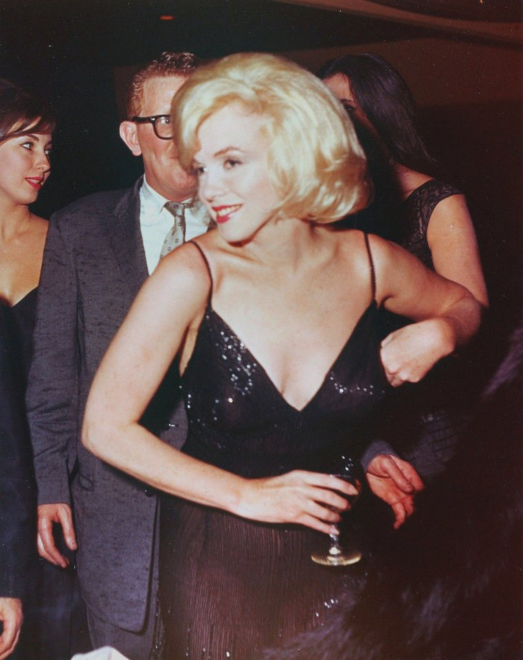 """1961 / Le 13 mars 1961, à New York, Marilyn participe au gala de charité """"The Roseland Dance Hall"""" organisé par les STRASBERG. Parmi les invités: Lee STRASBERG et sa femme Paula, l'actrice Vivien LEIGH et le réalisateur du film """"Arrêt D'autobus"""", Joshua LOGAN. Marilyn est arrivée accompagnée de John SPRINGER. Marilyn légua un manteau de fourrure en vison qui fut vendu aux enchères dont les profits allèrent à """"l' Actor's Studio Benefit"""". / La journaliste Danièle GEORGET et le photographe Caude AZOULAY, qui travaillent pour """"Paris Match"""", étaient présents. Il se souviennent : Claude AZOULAY : """"Il y avait une soirée à New York, pour le bal de l'Actors Studio. Elle était là, à cette soirée de gala, elle n'était pas très gaie. elle était nostalgique. Et à un moment, on appelle Marilyn au micro pour aller sur scène. Elle avait cette robe moulée magnifique. Alors, je la suis, elle quitte sa table, elle va et monte sur l'estrade, il y avait trois marches à monter. Et en montant les marches, 'crack', la robe se déchire juste derrière. Elle n'avait rien en-dessous ! Bon, elle monte et là, panique ou réflexe de Marilyn, devant toute la salle, alors qu'elle est sur scène, elle se retourne et fait """"Ouuuhhh"""" comme dans """"Certains l'aiment chaud""""; avec un grand sourire. On lui a amené son vison qu'elle a mis autour de sa taille. Et puis elle a fait son petit speech, c'était magnifique comme scène !"""" Danièle GEORGET : """"A la fin de la soirée, elle appuyait sa tête sur sa main. On voit qu'elle a trop picolé et qu'elle est d'une tristesse. Et là, c'est le contraire de la photo de star."""""""
