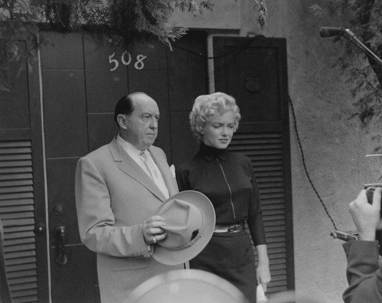 """1954 / La maison de """"North Palm Drive"""" fut assiégée par une centaine de journalistes et de photographes. Dans la villa, GIESLER (Avocat de Marilyn) était assis au chevet de Marilyn qui, au fond de son lit, subissait les effets  du sédatif administré par son médecin et ami, le gynécologue Leon KROHN. Elle signa un document d'une page et demie où elle réclamait le divorce en alléguant que pendant les huit mois que dura son mariage, elle avait enduré de « graves angoisses et souffrances morales et que tous les actes du défendeur n'étaient pas la conséquence d'une faute de la plaignante ». La plainte fit valoir que le couple s'était séparé le 27 septembre lorsque Joe était reparti sur la côte est, qu'il n'y avait pas de pension alimentaire, ni de propriété à partager. L'avocat Jerry GIESLER descendit retrouver Joe et lui tendit les papiers en l'informant qu'il avait dix jours pour contester cette demande avant qu'un décret par défaut ne soit prononcé. Joe ne dit rien, mit les papiers dans sa poche et se planta devant la télévision. GIESLER quitta la villa, avertissant les journalistes qu'une réconciliation semblait impensable mais que le divorce se déroulerait à l'amiable. Le mercredi 6 octobre : vers 10 heures, Joe avec Reno BARSOCCHINI, son ami et témoin du mariage avec  Marilyn, quitta la maison de """"North Palm Drive"""". Depuis sa voiture, il déclara aux journalistes qu'il se rendait chez lui, à San Francisco, et qu'il ne remettrait  pas les pieds à Los Angeles. Il est dit que Joe ne partit pas directement à San Francisco, mais qu'il alla  passer quelques jours chez le Dr Leon KROHN sur North Roxbury Drive, qui s'était autant attaché à Marilyn qu'à Joe. Selon KROHN, Marilyn appela Joe tous les soirs. Vers 10 h 55 Marilyn et son avocat, Jerry GIESLER, annoncèrent à la presse, devant la maison de """"North Palm Drive"""", qu'une procédure de divorce était engagée. Effondrée, elle se dirigea vers une voiture qui l'emmena d'abord chez Leon KROHN, ensuite au studio. Deux heures pl"""