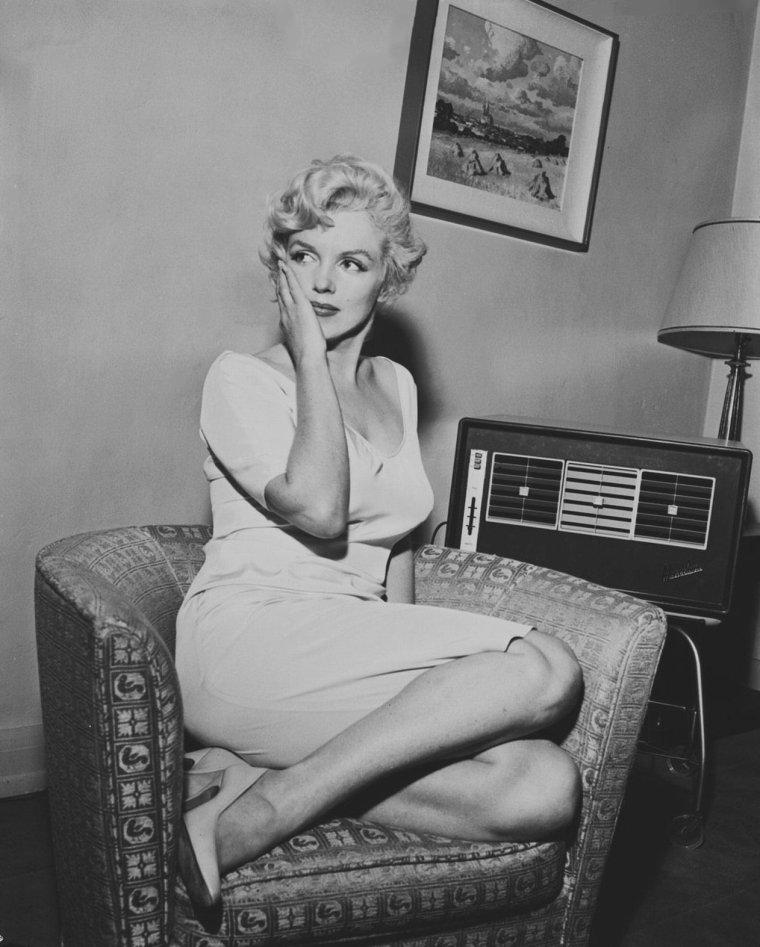 """1958 / Marilyn prend la pose sur un fauteuil le 8 août 1958, en attendant un coup de téléphone de son mari Arthur MILLER qui lui annonce le verdict de son procès : la cour d'appel des Etats-Unis a annulé la sentence de la comission sénatoriale le condamnant ; MILLER ajouta qu'il espérait que la décision """"mettrait un terme aux excès commis par les commissions et particulièrement à la pratique révoltante qui consistait à utiliser comme témoins à charge les amis ou des connaissances du passé"""". Quand à Marilyn, elle déclara à la presse : """"je suis heureuse pour mon mari mais je suis encore plus heureuse de constater que la vérité et la justice ne sont pas que des mots dans notre pays""""."""