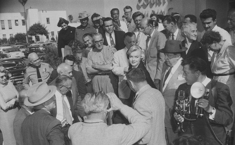 1954 / Divorce DiMAGGIO / Sidney SKOLSKY accompagna Marilyn et l'avocat Jerry GIESLER au tribunal de Santa Monica. Marilyn comparu devant le juge Orlando H. RHODES. Elle lui dira :  « Votre Honneur, mon mari était parfois d'une humeur si noire qu'il restait sans m'adresser la parole pendant cinq jours, même sept jours de suite. Encore plus même quelquefois. Je lui demandais : « qu'est-ce qui ne va pas ? ». Pas de réponse. Il m'interdisait de recevoir des visites ; en neuf mois, je n'ai reçu que trois fois des amis. La plupart du temps, il ne me témoignait que froideur et indifférence. » Natasha LYTESS s'était proposée de témoigner mais Marilyn l'en dissuada.  A la barre se présenta alors Inez NELSON  qui déclare d'une voix tranquille : «Mr DiMAGGIO était complètement différent et se souciait peu du bonheur de Mrs DiMAGGIO. Je l'ai vu la repousser et lui dire de lui ficher la paix ». Joe se tint à l'écart des débats, et Marilyn obtient un divorce provisoire (il ne deviendra effectif que dans un an), pour les raisons officielles suivantes : « Depuis le début de leur mariage, l'accusé a témoigné envers la plaignante d'une grande cruauté mentale, provoquant ainsi de graves souffrances psychiques, et une grande angoisse, tous actes et comportements de la part de l'accusé ne pouvant être imputés à la plaignante ; l'accusé est donc coupable d'avoir provoqué la détresse mentale de la plaignante, ses souffrances et son angoisse ». Le jugement définitif de divorce sera prononcé par le juge Elmer DOYLE, en faveur de Marilyn, pour le motif de cruauté mentale (équivalent à l'incompatibilité d'humeur dans notre code civil français) en 1955.