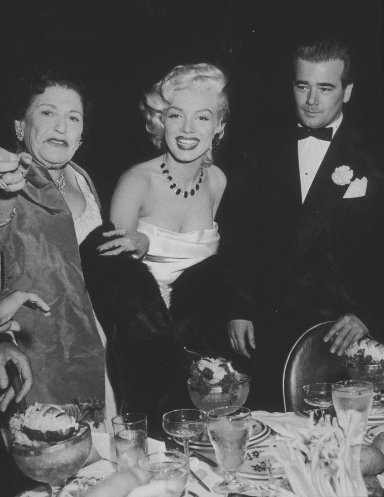 """1953 / 1er Janvier, Marilyn assista à la """"Cinemascope party"""", donnée au """"Cocoanut Grove"""" de """"l'Ambassador Hotel"""" de Los Angeles. Donald O'CONNOR, son futur partenaire de « There's no business like show business »,  la journaliste Louella PARSONS, le compositeur Cole PORTER et  Joe DiMAGGIO assistèrent également à la soirée. Marilyn et Joe firent un pacte : elle s'engageait à ne plus porter en publique ses robes décolletées qui le gênaient tant, et il essayerait de se montrer plus patient avec elle et plus poli avec Natasha LYTESS, pour qui il éprouvait toujours une antipathie égale sans doute à celle qu'elle-même éprouvait à son égard."""