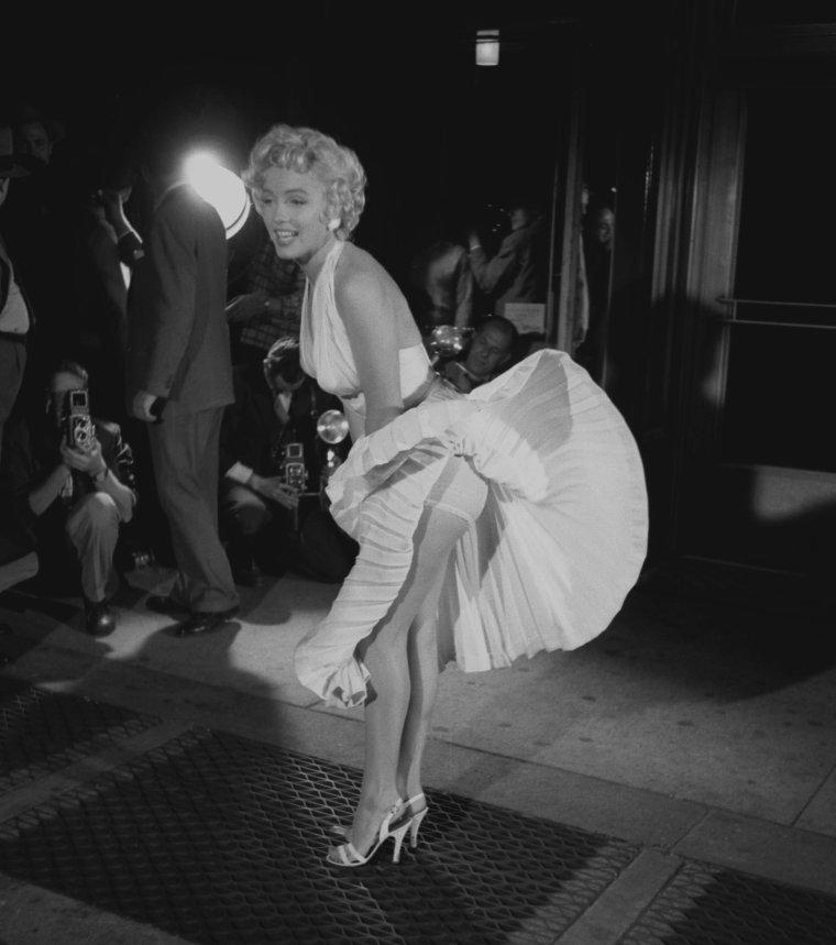 """1954 / by George S ZIMBEL... Scène culte / Le tournant décisif de l'union de Joe et Marilyn, eut lieu le mercredi 15 septembre, jour où le journaliste Walter WINCHELL persuada Joe de se joindre à la foule de plusieurs centaines de curieux qui attendaient pendant des heures, devant le """"Trans-Lux Theater"""", sur Lexington Avenue au coin de la 52nd Street, pour voir enfin la jupe plissée de Marilyn s'envoler, en dévoilant ses jambes, au dessus d'une bouche de métro. La scène fut tournée vers une heure du matin, au milieu d'une foule qui poussait des hourras chaque fois que la jupe de Marilyn s'envolait, sous l'effet du courant d'air provoqué par un énorme  ventilateur installé en dessous d'une grille de métro. Il y eut quinze prises et le tournage dura cinq heures. Le tournage de cette scène était essentiellement publicitaire : en effet tout le monde savait qu'elle serait de toute façon tournée au studio de la Fox car les bruits ambiants couvraient complètement les dialogues, il n'y avait pas assez de liberté de mouvement à cause de la foule et le ventilateur utilisé ne produisait pas l'effet désiré. Sur le tournage elle eut la visite du journaliste Earl WILSON accompagné par l'actrice italienne Gina LOLLOBRIGIDA.  Amy et Milton GREENE étaient également présents aux côtés de Joe. La scène et les acclamations du public mirent Joe dans une colère noire : il devint fou de rage et rentra immédiatement au """"St Regis Hotel"""". Au retour de Marilyn à l'hôtel, ils eurent une violente altercation, et l'on rapporte que Joe devint brutal. On entendit des pleurs et des éclats de voix provenant de leur chambre. Le lendemain, Marilyn arriva pleine d'ecchymoses sur le tournage. Whitey SNYDER la maquilla et camoufla les bleus."""
