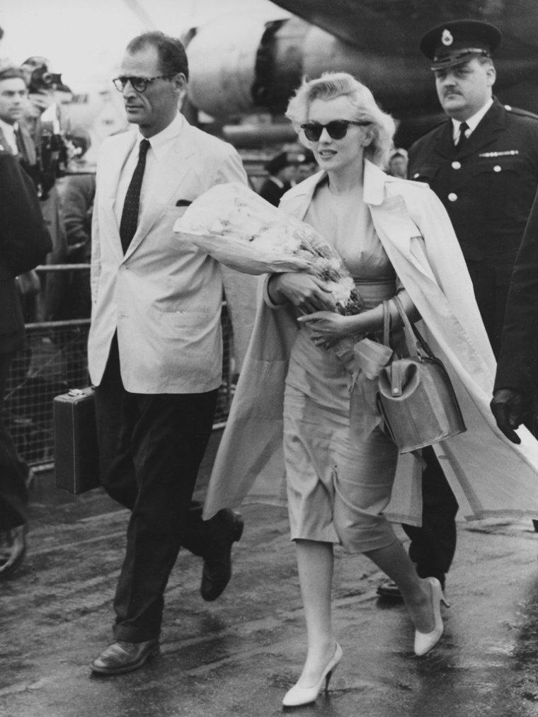 """1956 / Le 13 juillet 1956, Marilyn et Arthur partent de New York pour se rendre en Angleterre où Marilyn doit tourner """"The Prince and the Showgirl"""" (Le prince et la danseuse). Une foule de personnes s'est regroupée à l'aéroport new-yorkais pour apercevoir le couple qui prend l'avion. De nombreux journalistes de la presse écrite et aussi des caméras, sont sur les lieux (pas moins de 70 policiers pour canaliser la foule et plus de 200 journalistes). La presse va rapporter que le couple voyage avec 27 valises."""