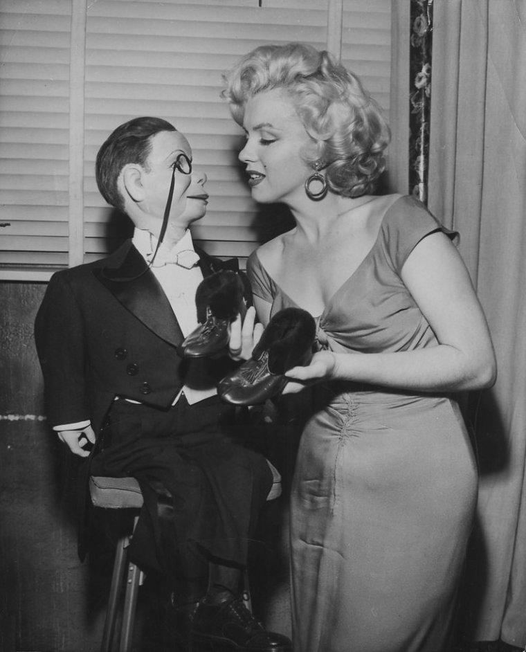 """1952 / Le 26 octobre 1952, Marilyn est invitée au show radiophonique d'Edgar BERGEN, un ventriloque, qui animait une émission avec deux marionnettes : Charlie McCARTHY et Mortimer SNERD. Marilyn s'est prêtée au jeu, prenant des poses de séductrice avec les pantins. Elle était vêtue de la fameuse robe rouge du film """"Niagara""""."""
