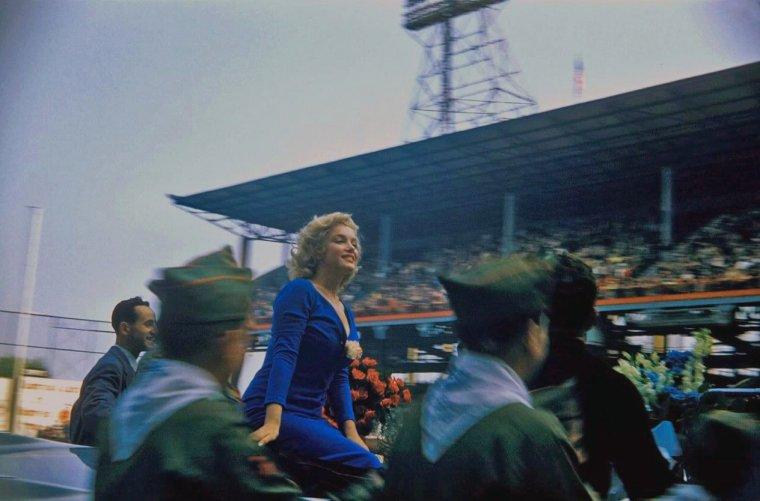 """1957 / by Bob HENRIQUES and Sam SHAW... Le 12 mai 1957 Marilyn donne le coup d'envoi du match de football USA vs ISRAËL au stade d' """"Ebbets Field"""" à Brooklyn (quartier de New York). C'est une Marilyn enjouée et resplendissante, vêtue d'une robe d'un bleu vif, qui se rend à cette manifestation publique, suivie par des milliers de spectateurs. Arrivée en voiture décapotable qui a fait le tour du stade, Marilyn salue le public et signe des autographes. Enthousiasmée, elle tape si fort dans la balle qu'elle se foule un orteil !"""