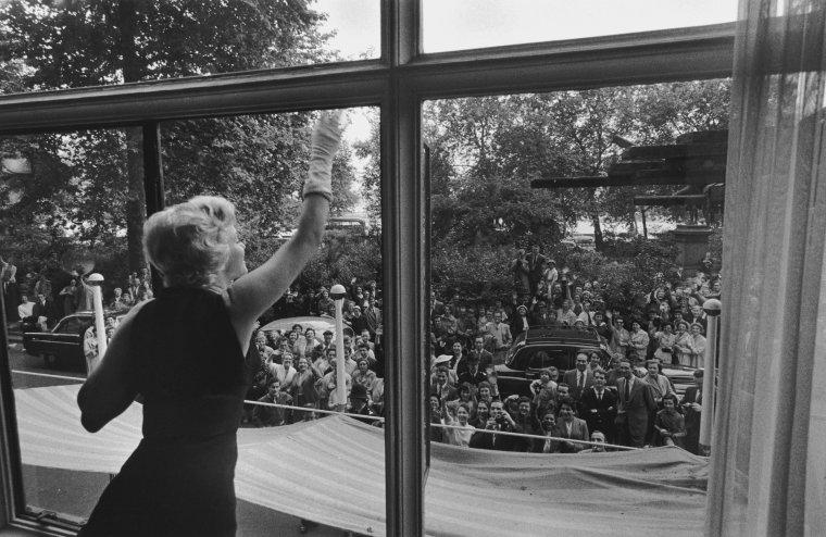 """1956 / Les MILLER s'installèrent à """"Parkside House"""", à Englefield Green, Egham (près de """"Windsor Park"""", à une heure de route de Londres). Ils louèrent le superbe manoir géorgien à Lord NORTH, directeur du """"Financial Times"""" et à sa femme l'actrice et pianiste Joan CARR. Ce manoir du XVIIIème siècle comptait cinq chambres, une salle de séjour avec des poutres en chêne, deux salles de bains et  des chambres de service et était entouré d'un parc d'environ cinq hectares avec une roseraie. Dans cette maison, de lourds doubles rideaux avaient été installés aux fenêtres de la chambre de Marilyn, car elle ne pouvait dormir que dans le noir absolu. La chambre, à l'initiative de Milton GREENE, avait aussi été meublée de blanc (lit, rideaux, meubles, tapis) comme dans son appartement new-yorkais. Dans la plus pure tradition britannique, les journalistes assiégèrent le portail de la propriété durant tout leur séjour. Le dimanche 15 juillet : après une séance photo à Egham, une conférence de presse avec Marilyn, MILLER et Laurence OLIVIER fut donnée dans la salle """"Lancaster"""" de """"l'hôtel Savoy"""" de Londres pour annoncer le début du tournage de """"The prince and the showgirl""""."""