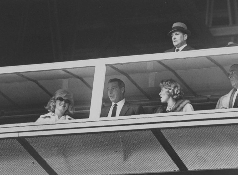 "1961 / Marilyn et Joe assistent au match d'ouverture de la saison de base-ball, entre les ""New York Yankees"" et  les ""Minnesota Twins"", au ""Yankee Stadium"" de New York."