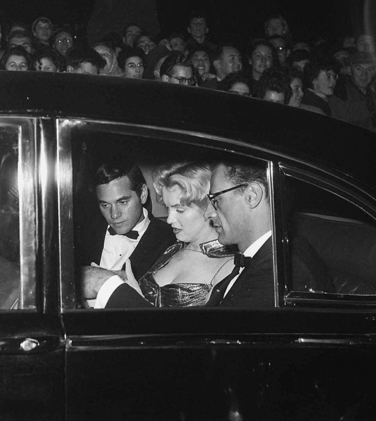 """1956 / Marilyn fut présentée à la reine d'Angleterre Elizabeth II, à """"l'Empire Theatre"""", à Leicester Square. Avant une projection du film britannique « The battle of the river plate », vingt vedettes de cinéma furent présentées à la reine, dont Brigitte BARDOT, Joan CRAWFORD, Anita EKBERG ou Victor MATURE. Elle sera immortalisée peu après au musée de cire de Mme TUSSAUD."""