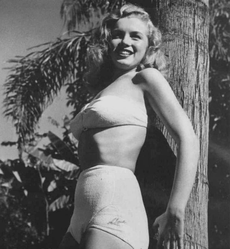 """1945-46 / Norma Jeane signa son contrat avec la """"Blue Book Modeling Agency"""", et à dix-neuf ans, quitta la """"Radio Plane Munitions Factory"""" où elle travaillait depuis 1944. Elle donna 25 $ pour avoir sa photo dans le catalogue de l'agence.  Elle suivit assidûment des cours de maquillage et de soins de beauté (avec Maria SMITH), de mode (avec Mrs Gavin  BEARDSLEY) et de maintien (avec Miss SNIVELY). Le prix des cours était de 100 $, qui seront déduits de son premier salaire. SEPTEMBRE : La """"Blue Book Modeling Agency"""" lui trouva immédiatement un travail  comme hôtesse d'accueil pour une foire industrielle  organisée par la """"Holga Steel Company"""" au """"Pan Pacific Auditorium"""" (7600 Beverly Boulevard). Elle travailla dix jours pour 100 $ (soit 10 $ par jour). Puis elle fit deux jours de pose pour le catalogue de vêtements de Montgomery WARD et défila pendant quatre jours pour le """"Hollywood Fashion Show"""". Elle fit une séance publicitaire pour le DC-6 de la compagnie aérienne de """"luxe Douglas"""", publicité qui sortira en 1946. Ethel DOUGHERTY (sa belle-mère) se mit à critiquer le comportement de sa belle-fille : elle prétendit que la carrière de modèle était incompatible avec la dignité d'une femme mariée, appelée à être mère. Ethel n'appréciait pas non plus que Norma Jeane mène une vie sociale indépendante. Ne supportant plus les regards désapprobateurs d'Ethel, Norma Jeane retourna s'installer chez Ana LOWER (11348 Nebraska Avenue, West Los Angeles). Elle laissa aux DOUGHERTY son chien Muggsy, qui mourra quelques mois plus tard."""